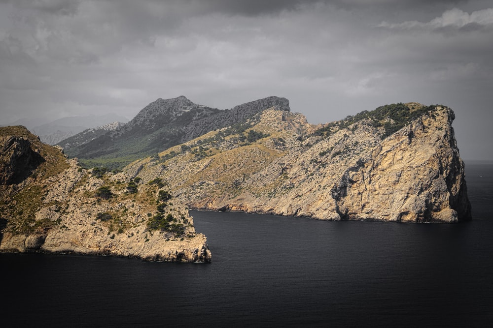 high angle photography of mountain cliff near body of water