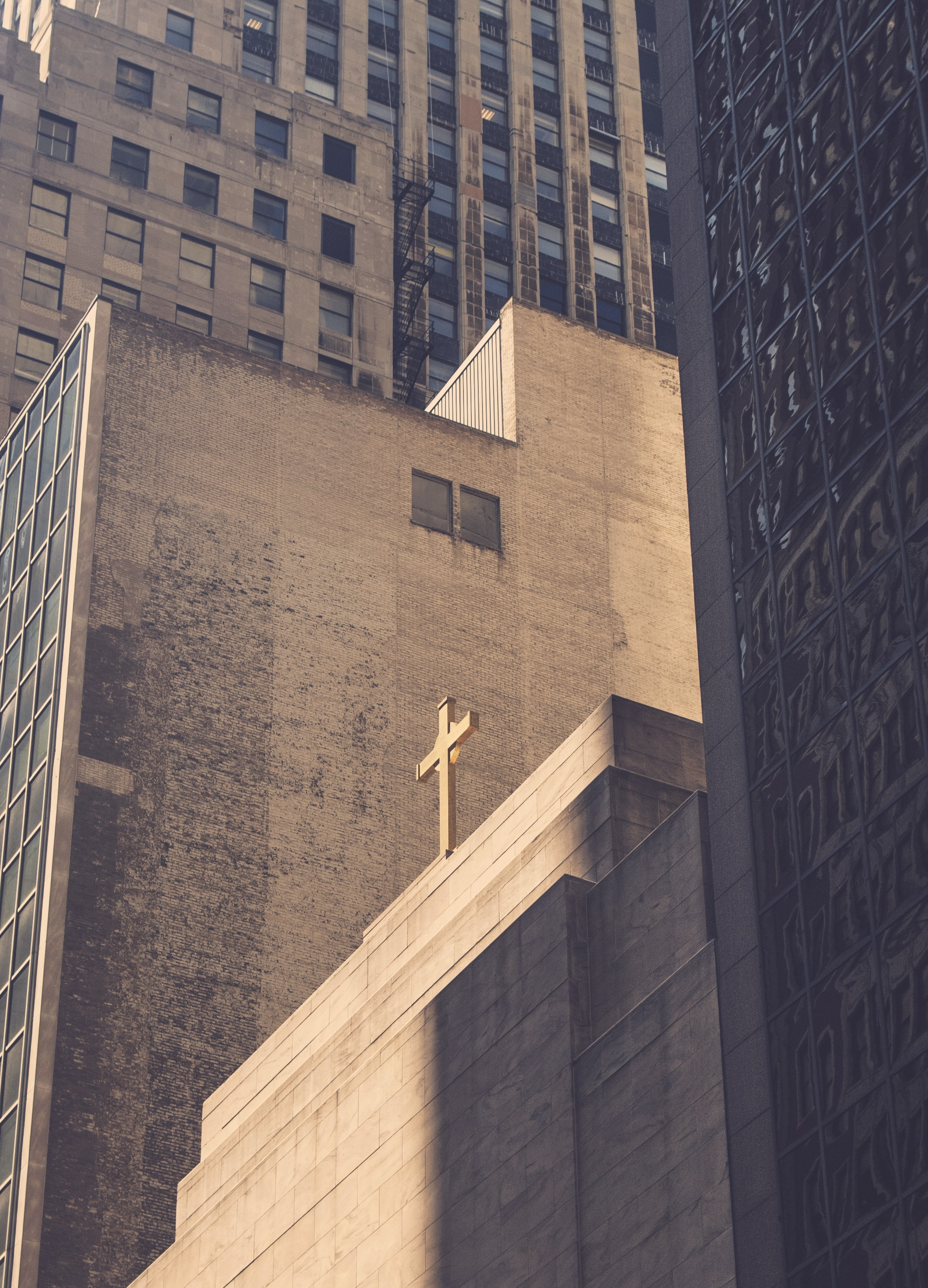 Cross on a simple concrete church building surrounded by high rise buildings