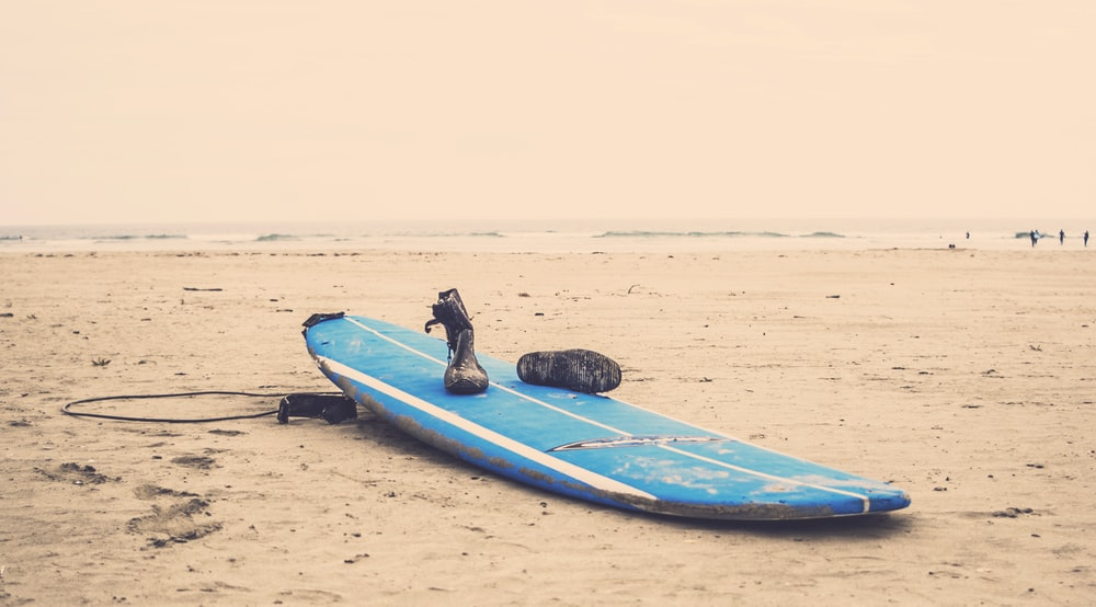 blue surfboard on gray sand