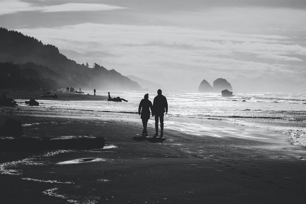 grayscale photo of man and woman walking on seashore