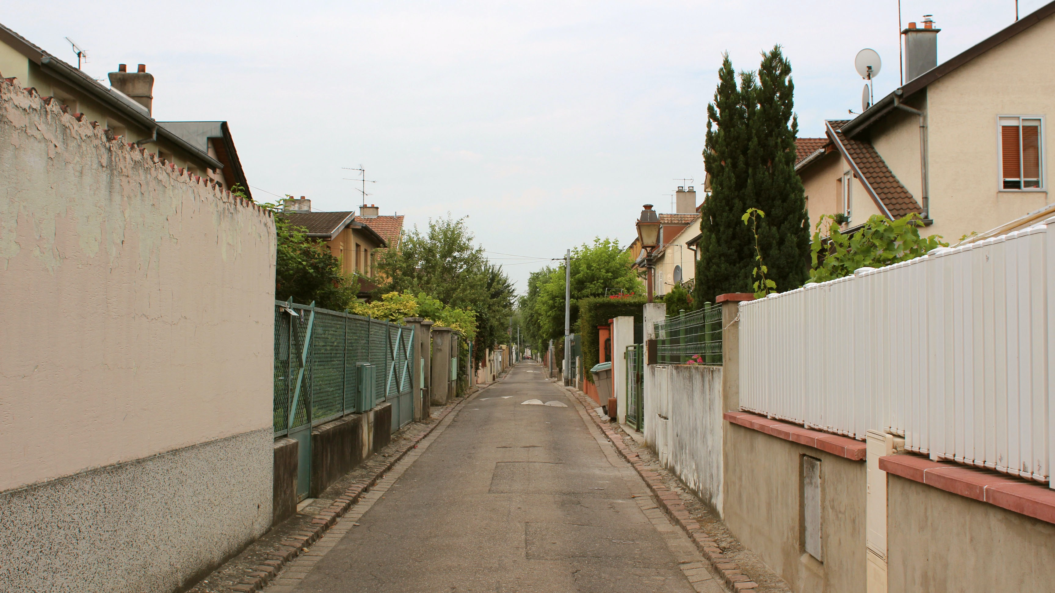 Street in an urban setting with fences surrounding houses along the road