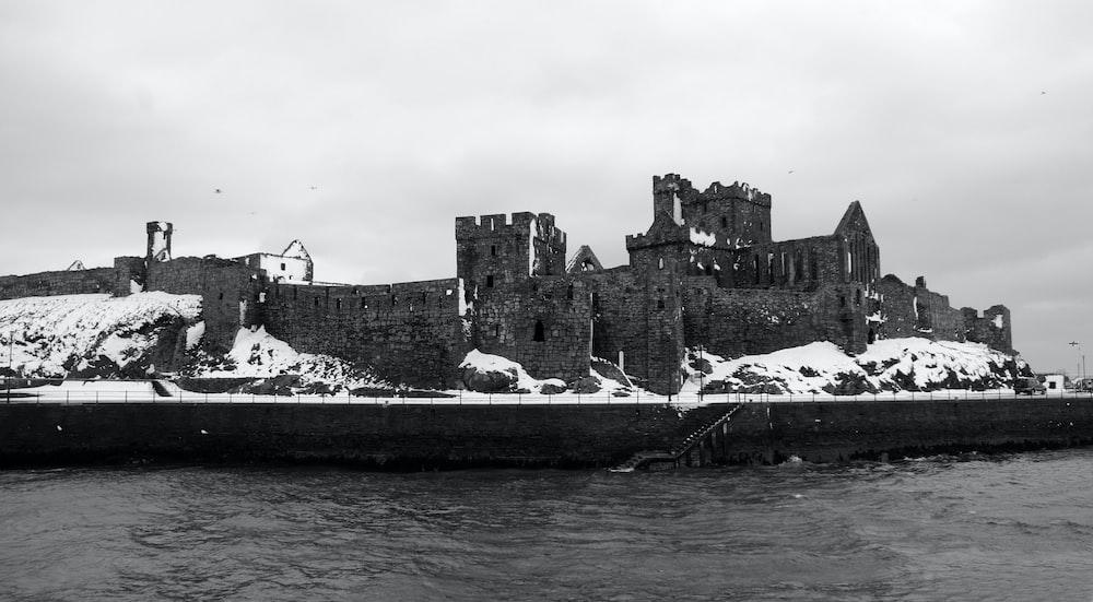 grayscale photo of concrete castle beside sea