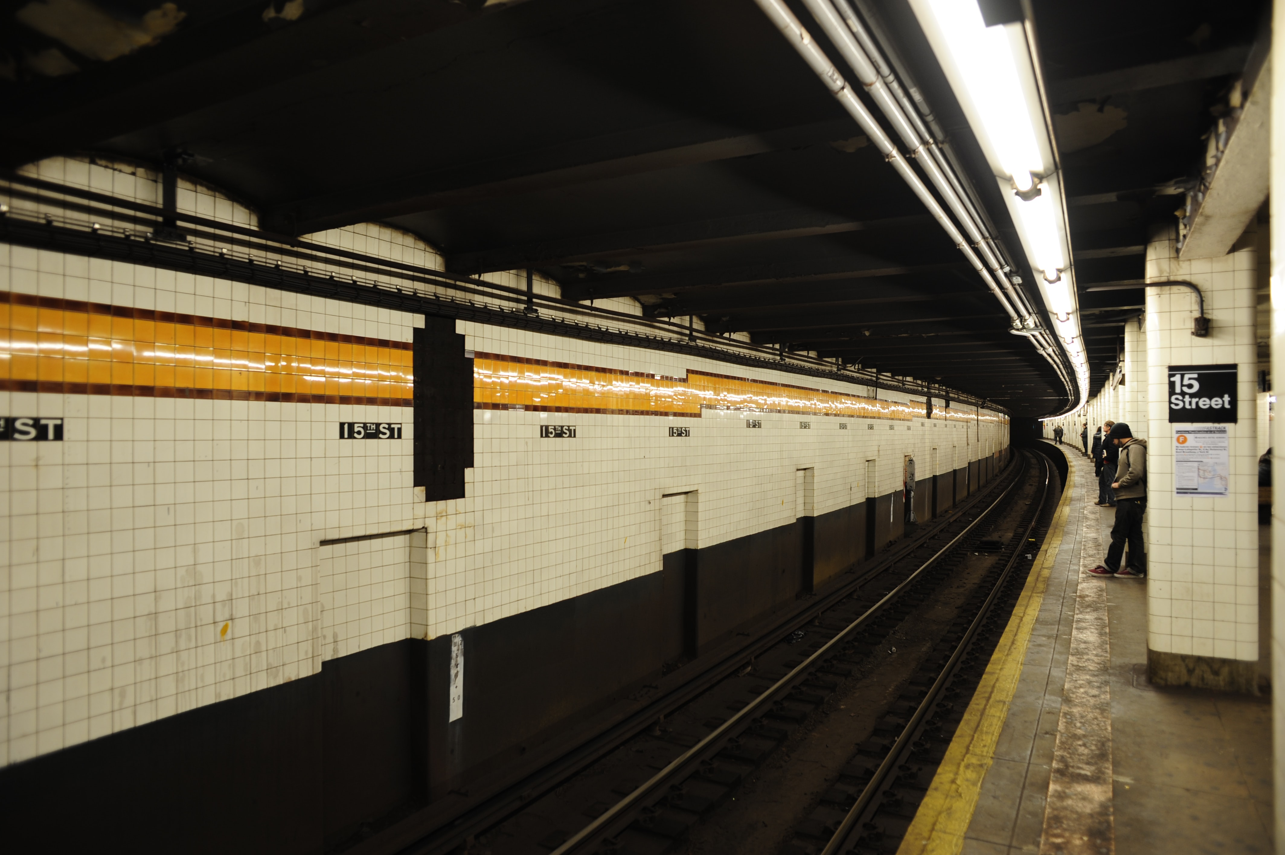New York City underground subway station with people waiting for their train
