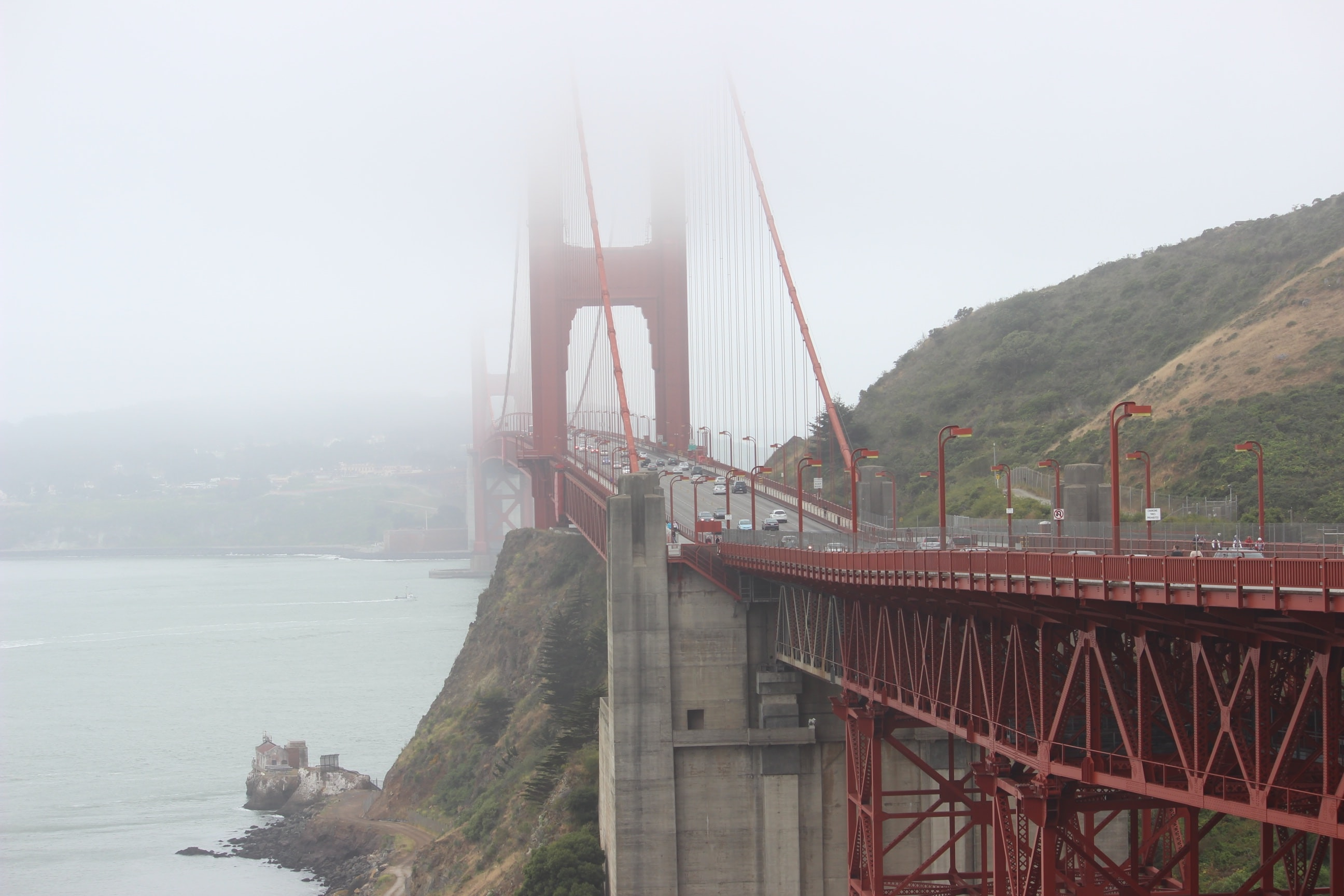 Long shot of misty Golden Gate Bridge in San Francisco with busy daytime traffic