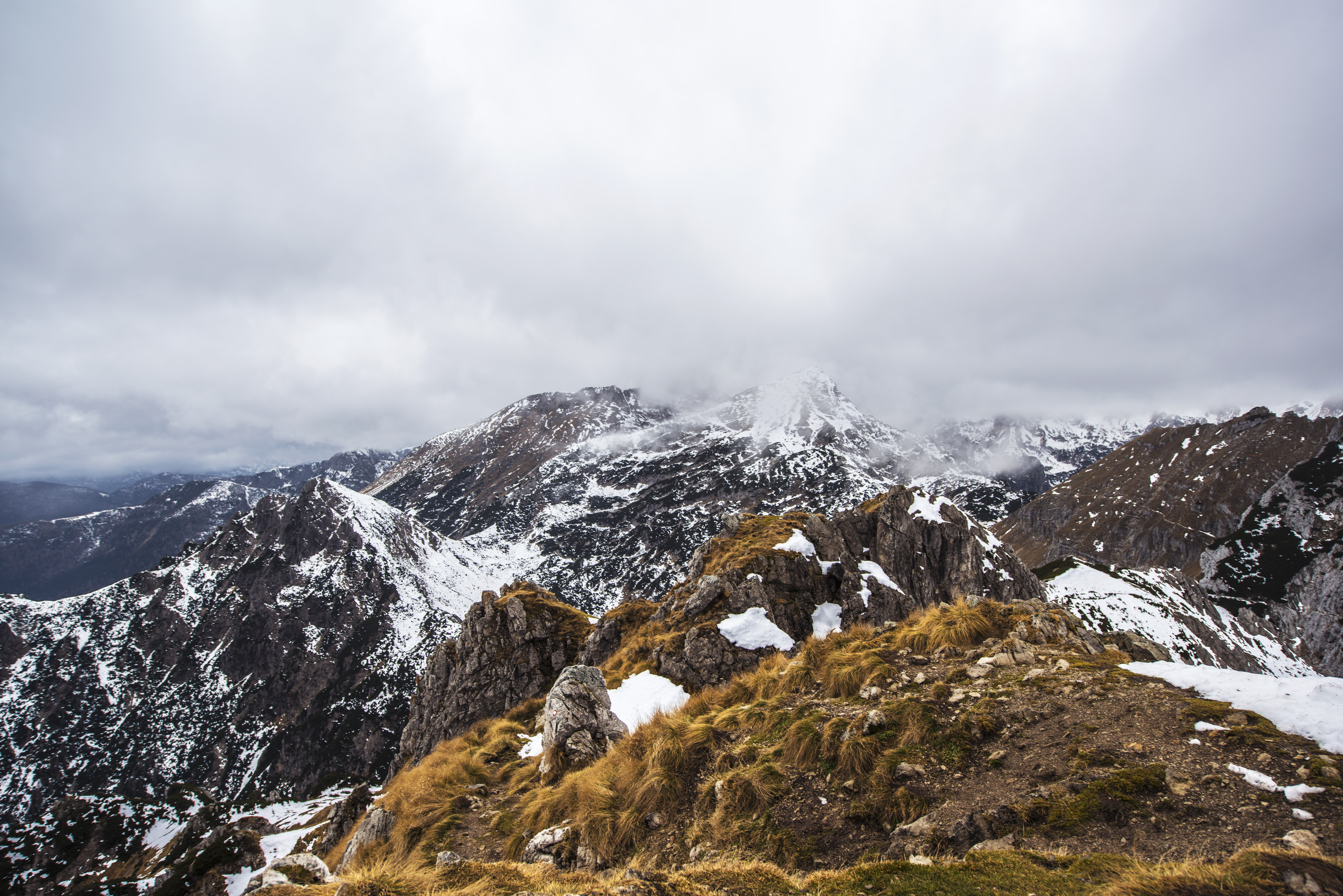 A mountainous landscape with jagged snowy ridges enveloped by thick clouds