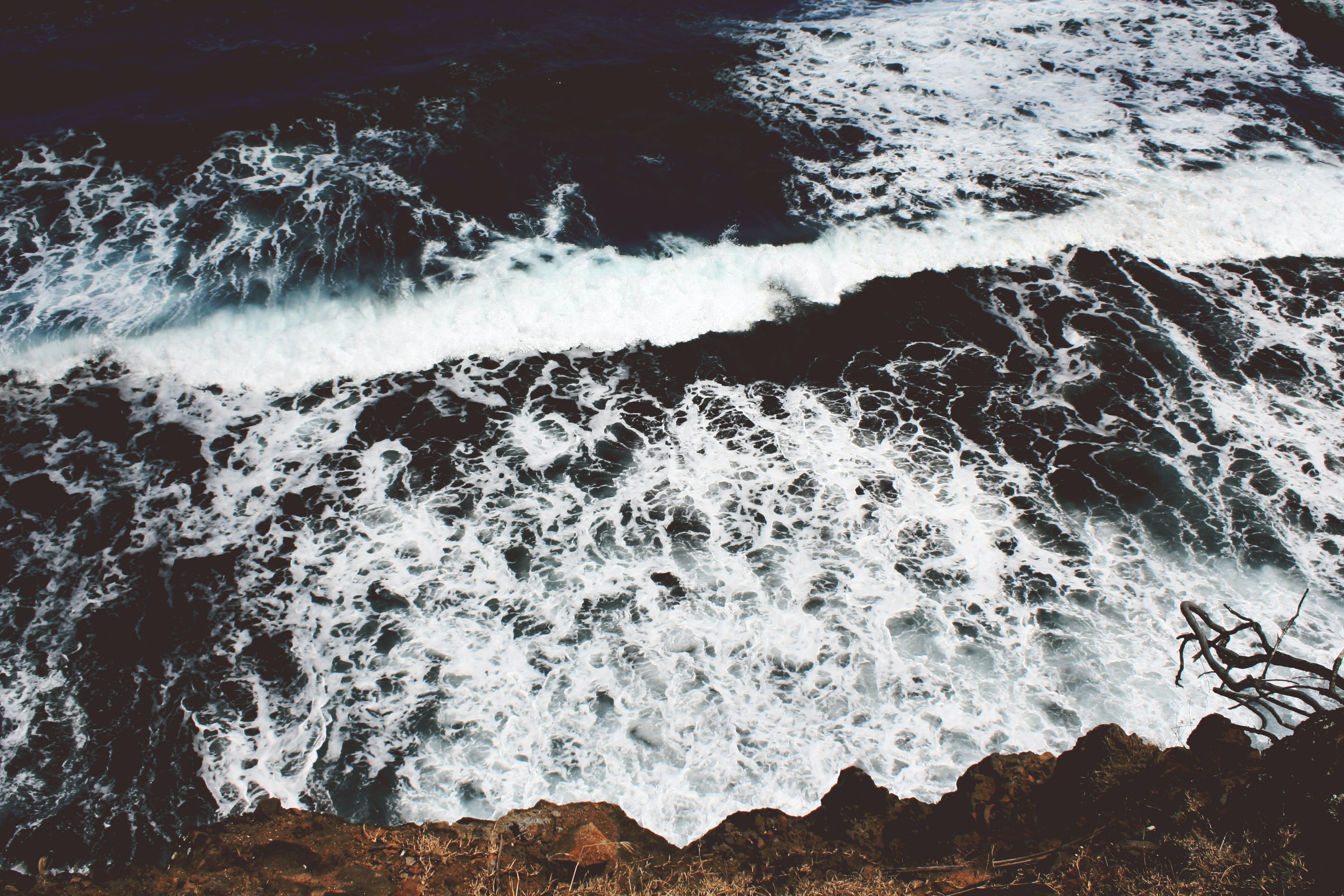 Frothy sea waves crashing against a rocky cliff