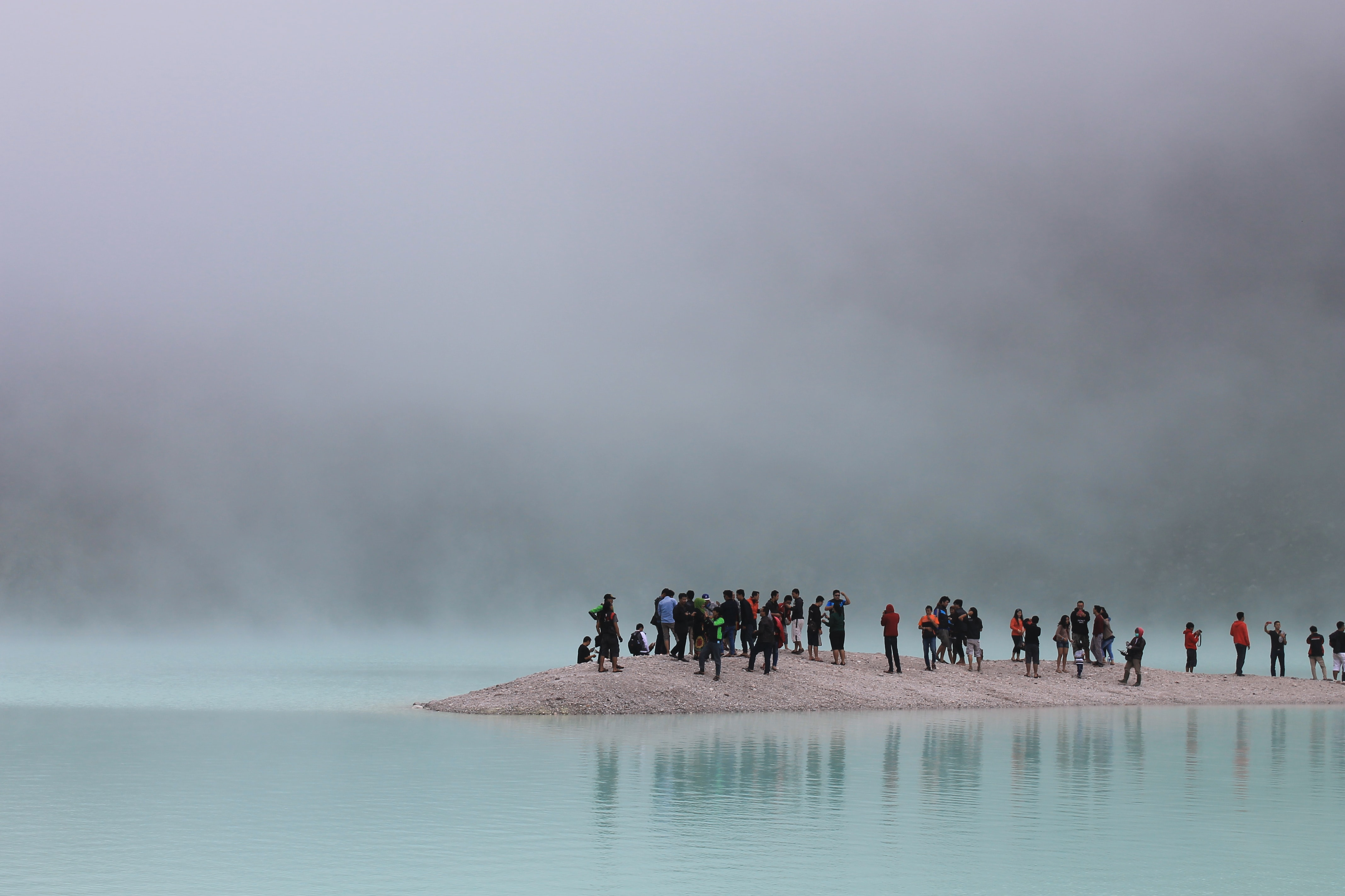 Diverse group of tourists stand on a peninsula on a foggy day