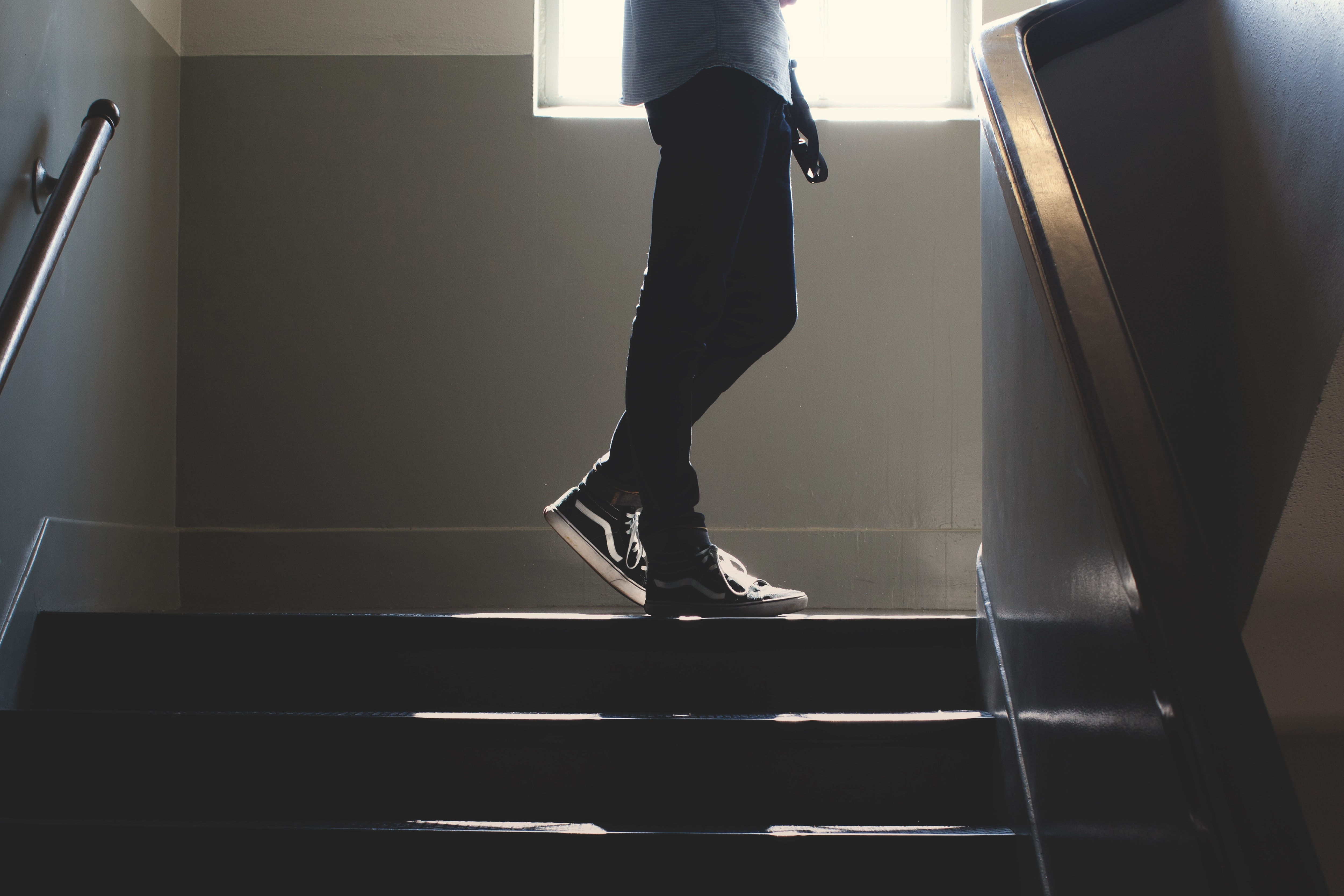 A hipster boy standing in a stairwell wearing Vans