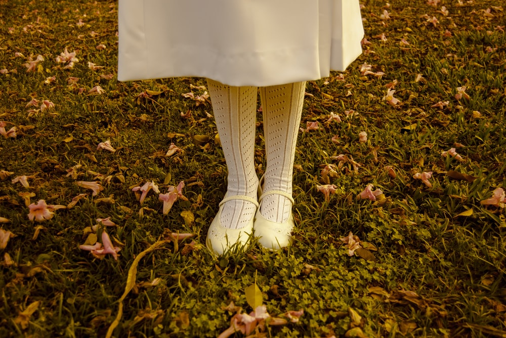 girl standing on grass wearing white dress and shoes during daytime