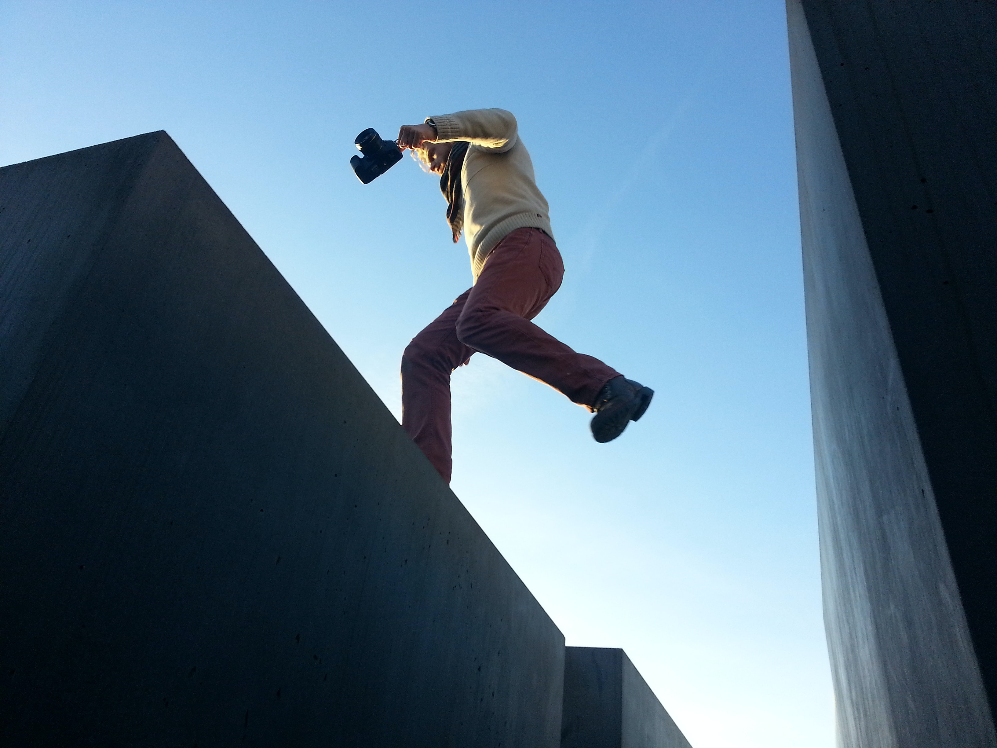 A man jumping between a gap on a roof