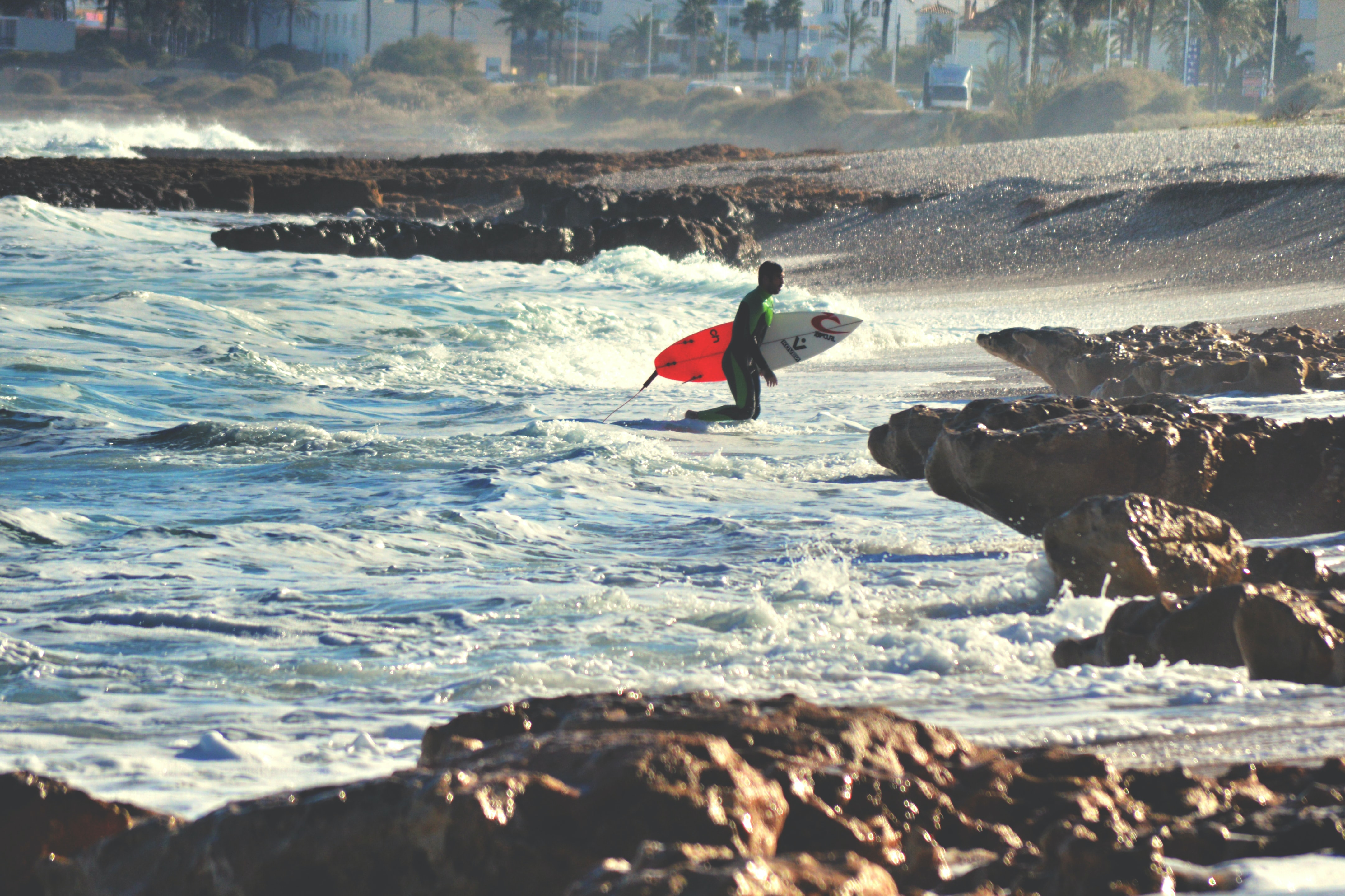 A guy standing in the rocky sea holding a surfboard in the ocean