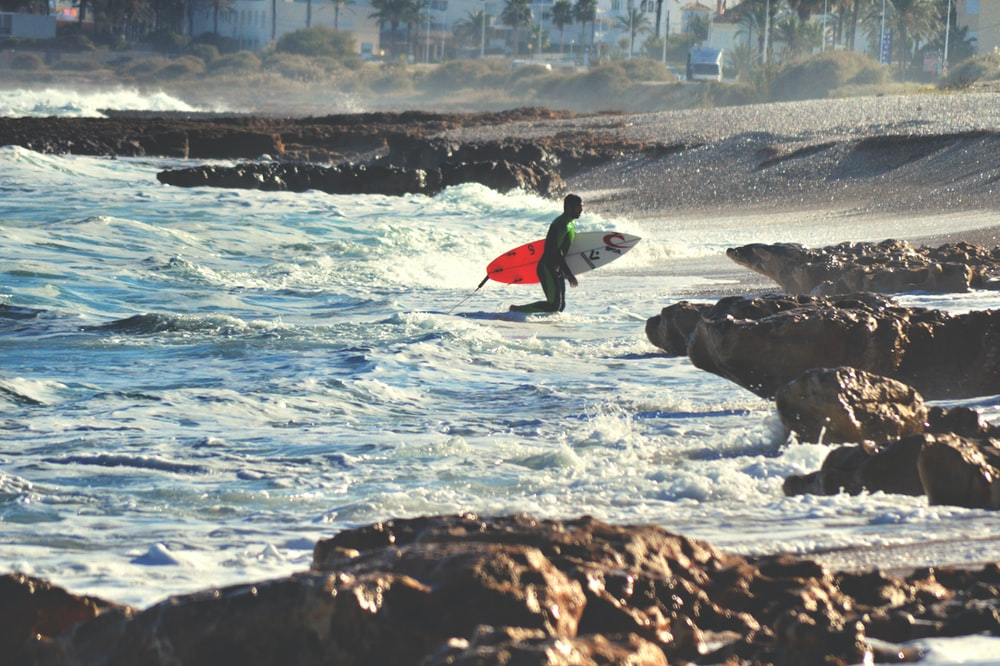 surfer walking on body of water during daytime