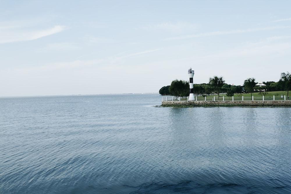 white and black light house beside of blue ocean during daytime