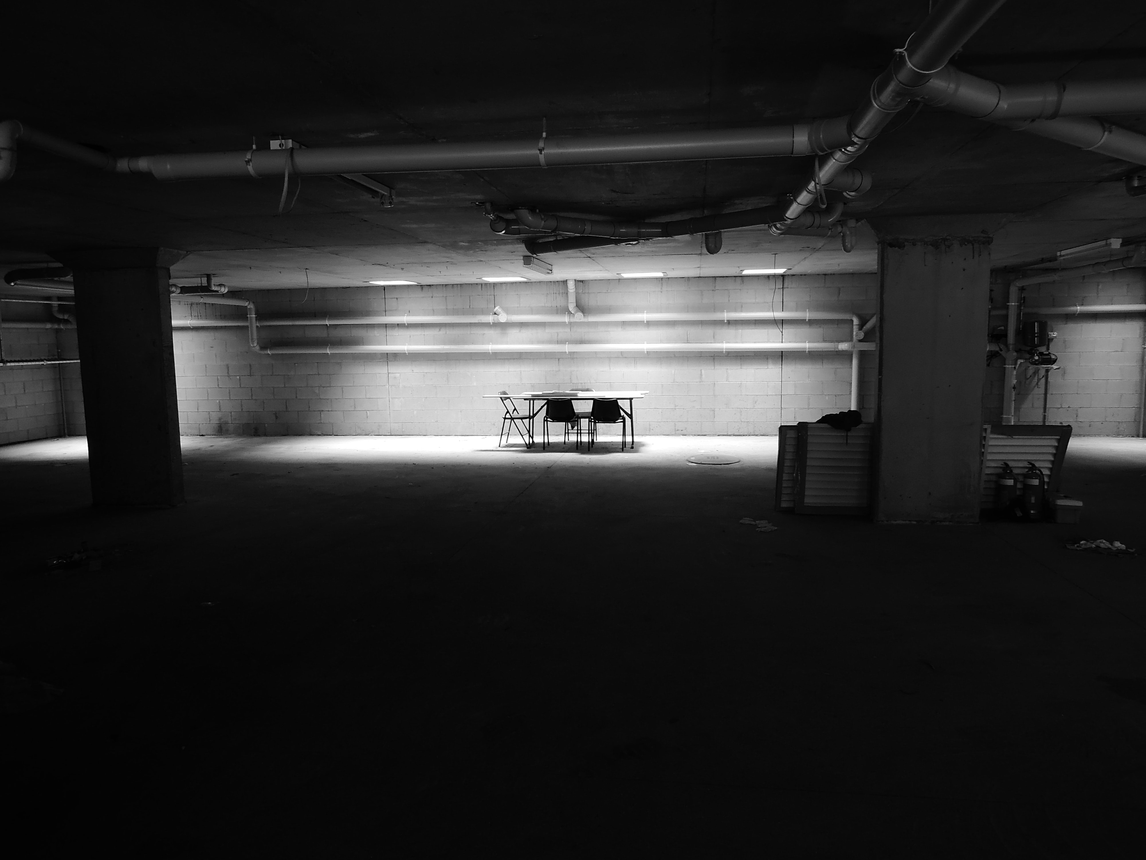 An empty table with chairs in a dark basement