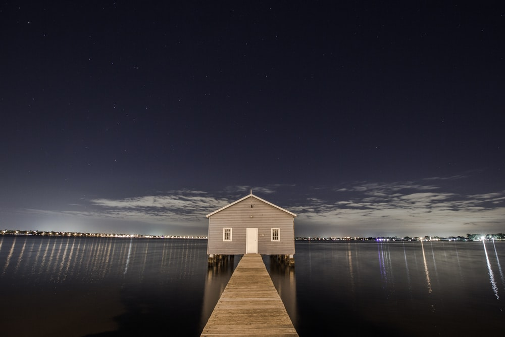 white and gray wooden house in the middle of body of water