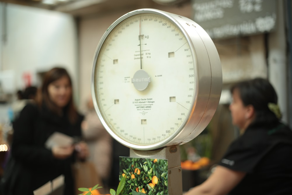 A large market Sauter scale next to picture of oranges and a checkout line