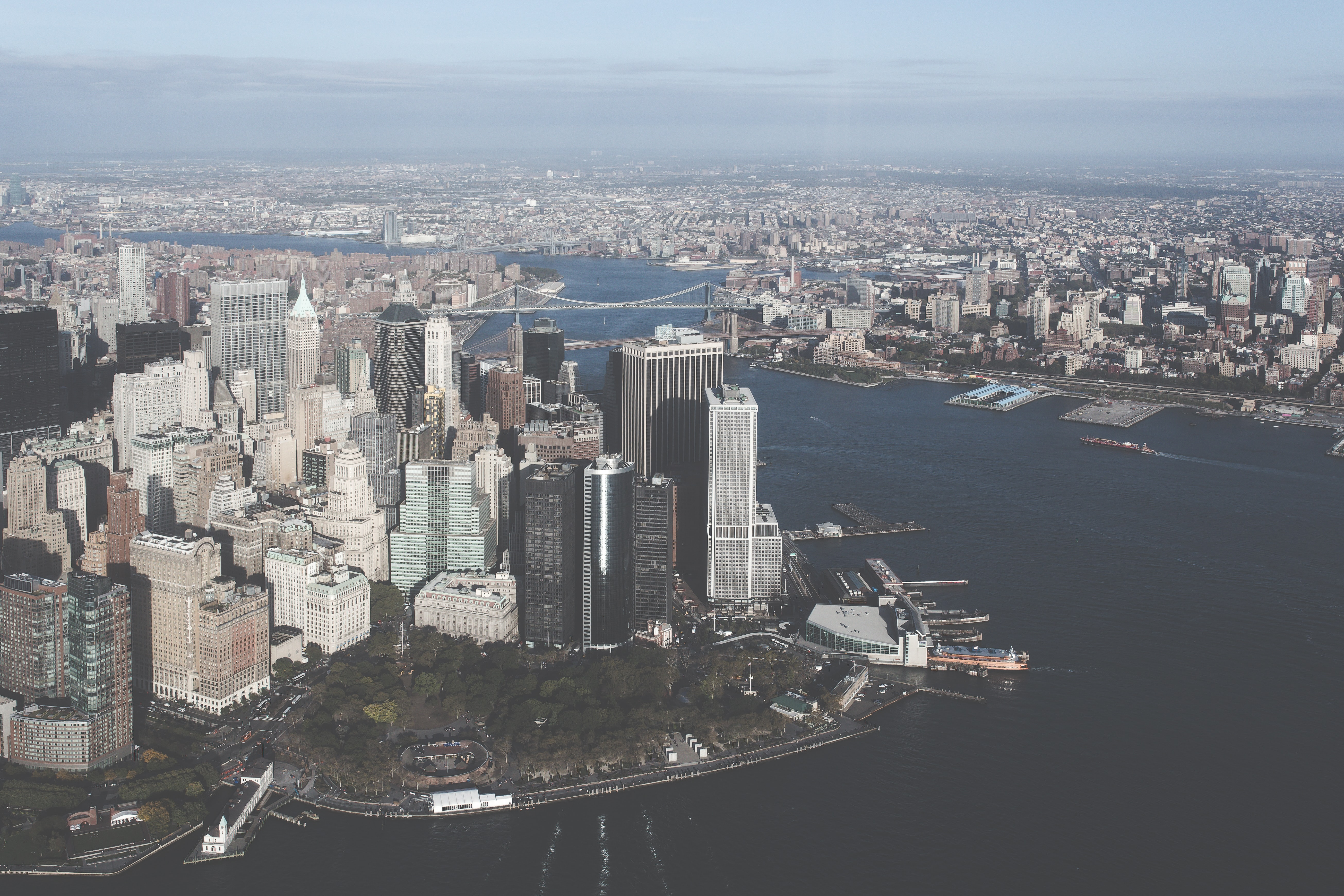 A cityscape view showing a business area with sky scrapers and a riverside harbor in the New York city