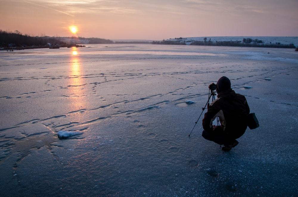 man taking photo of sunset