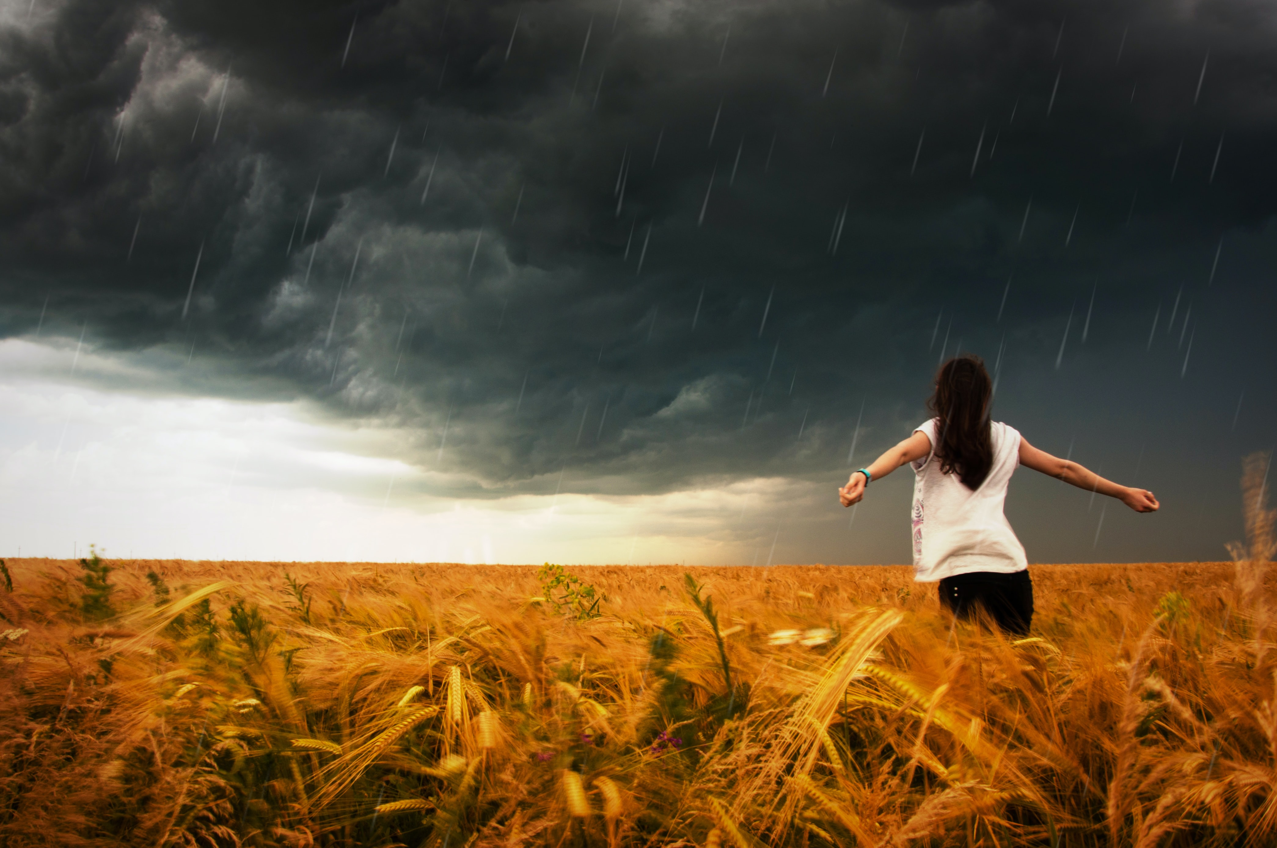 A woman holding her arms out and embracing the incoming storm.