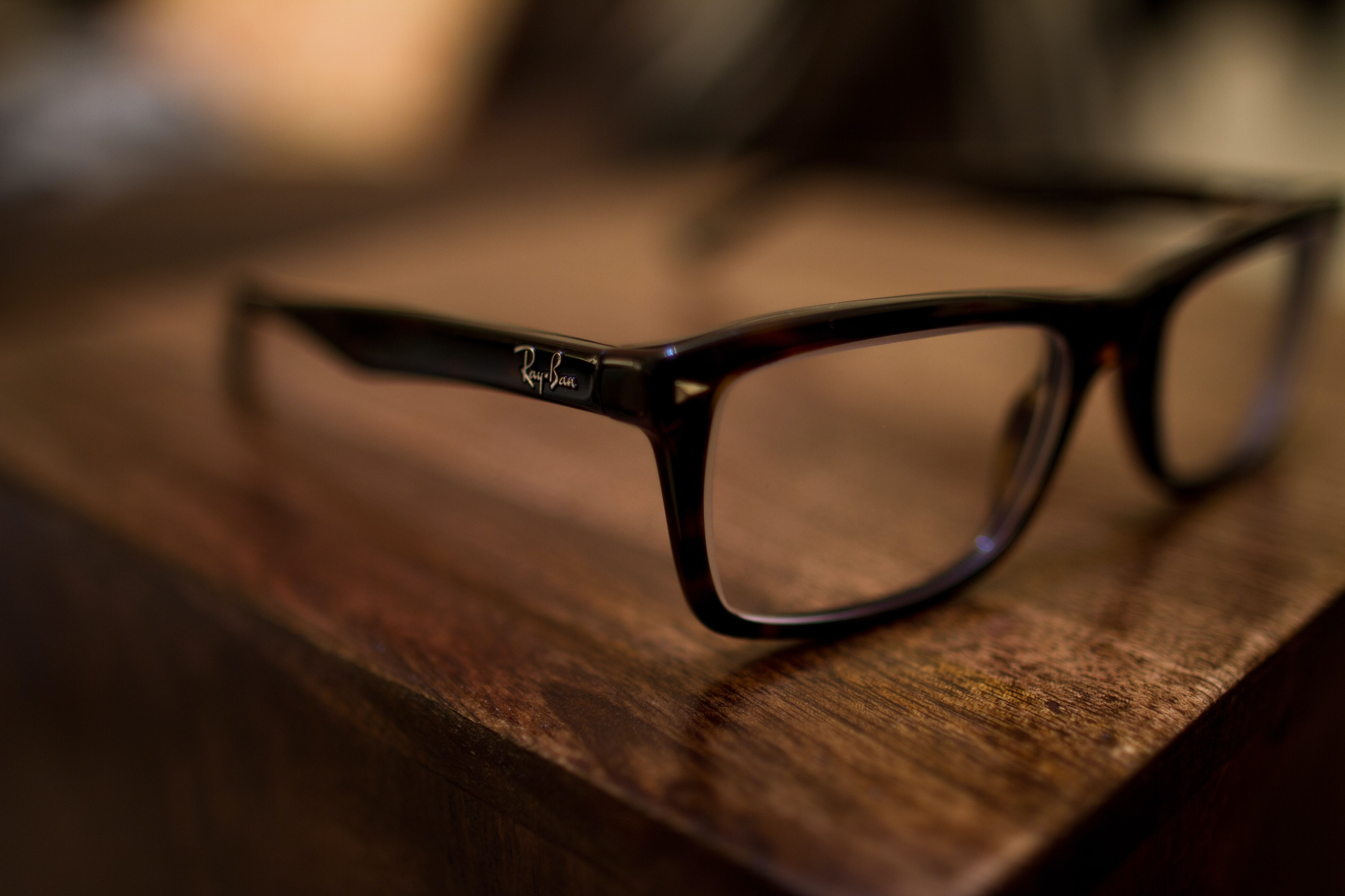 eyeglasses with black frames on brown table