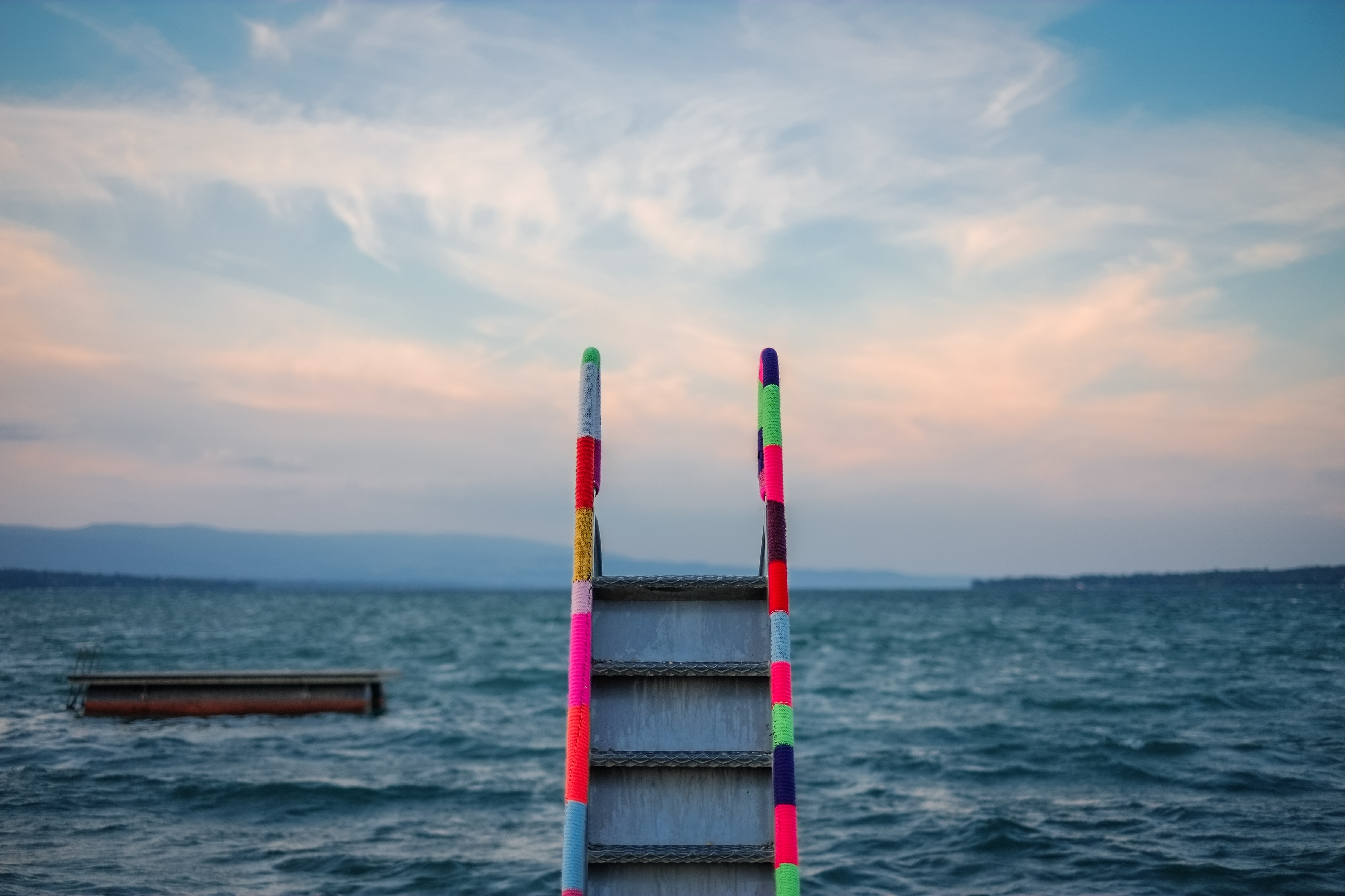 A striped, colored ladder staircase leading to the ocean water