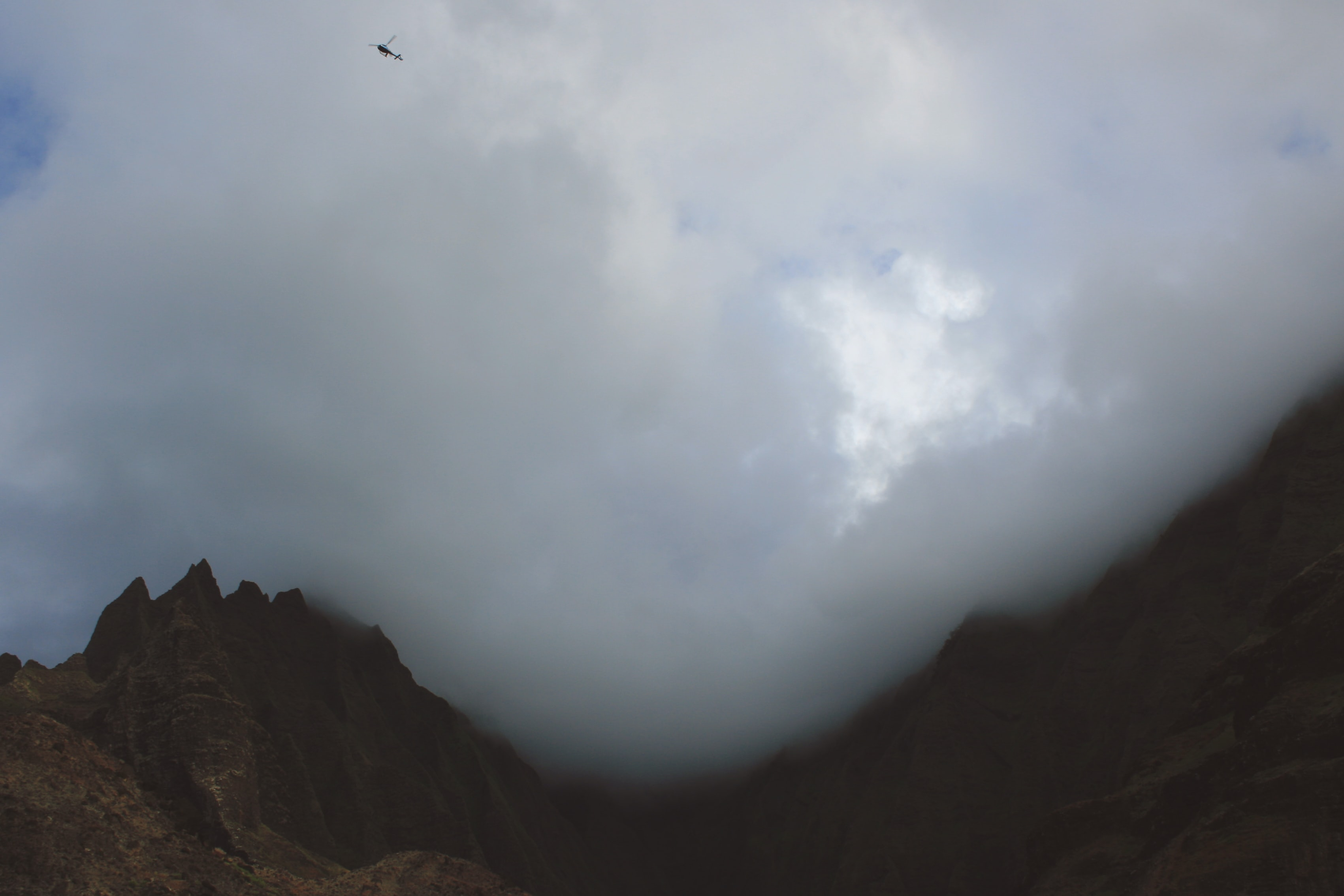 A helicopter flies through billowing clouds over a mountain landscape