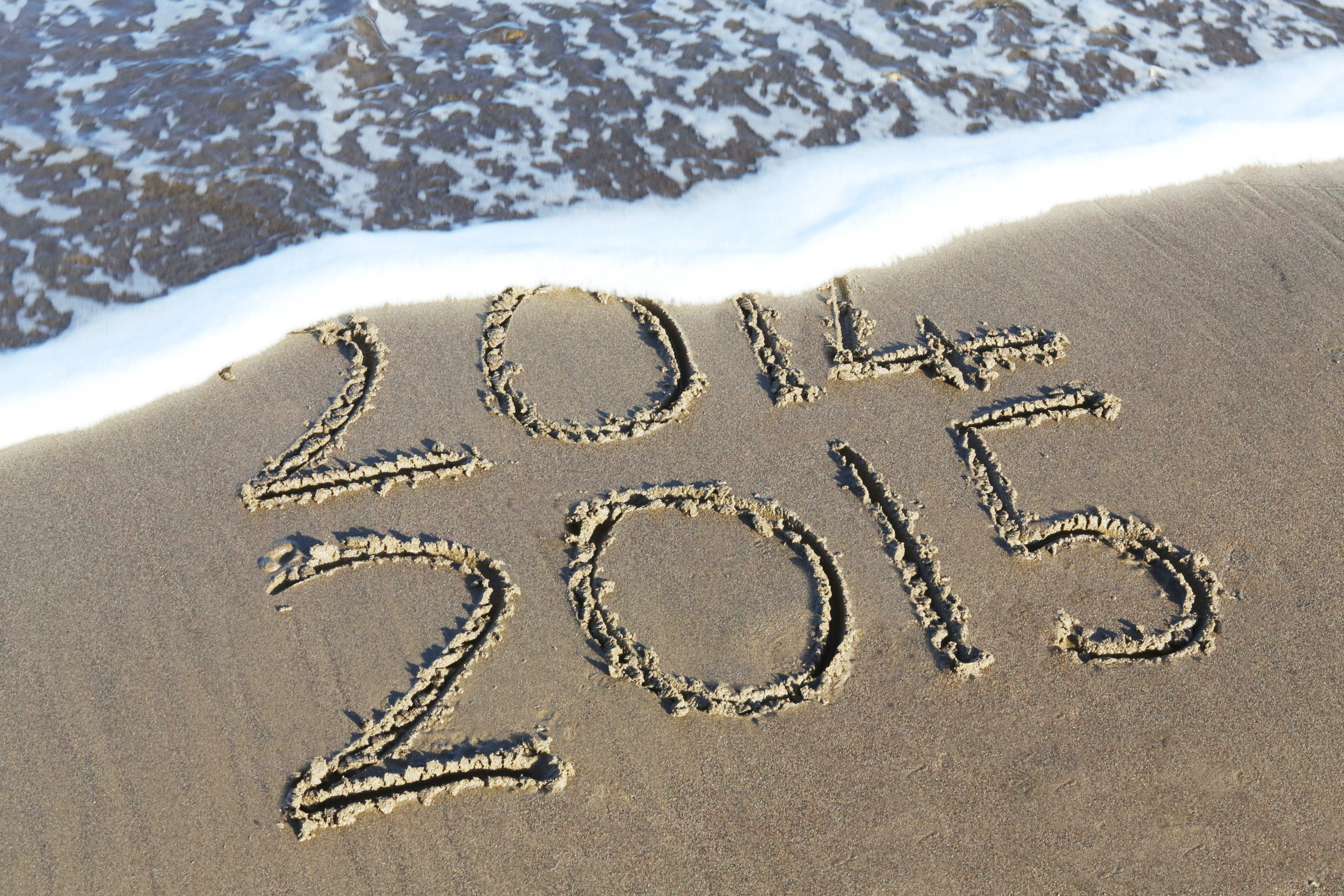 Tide covering inscription of the old year above the new year n the sand