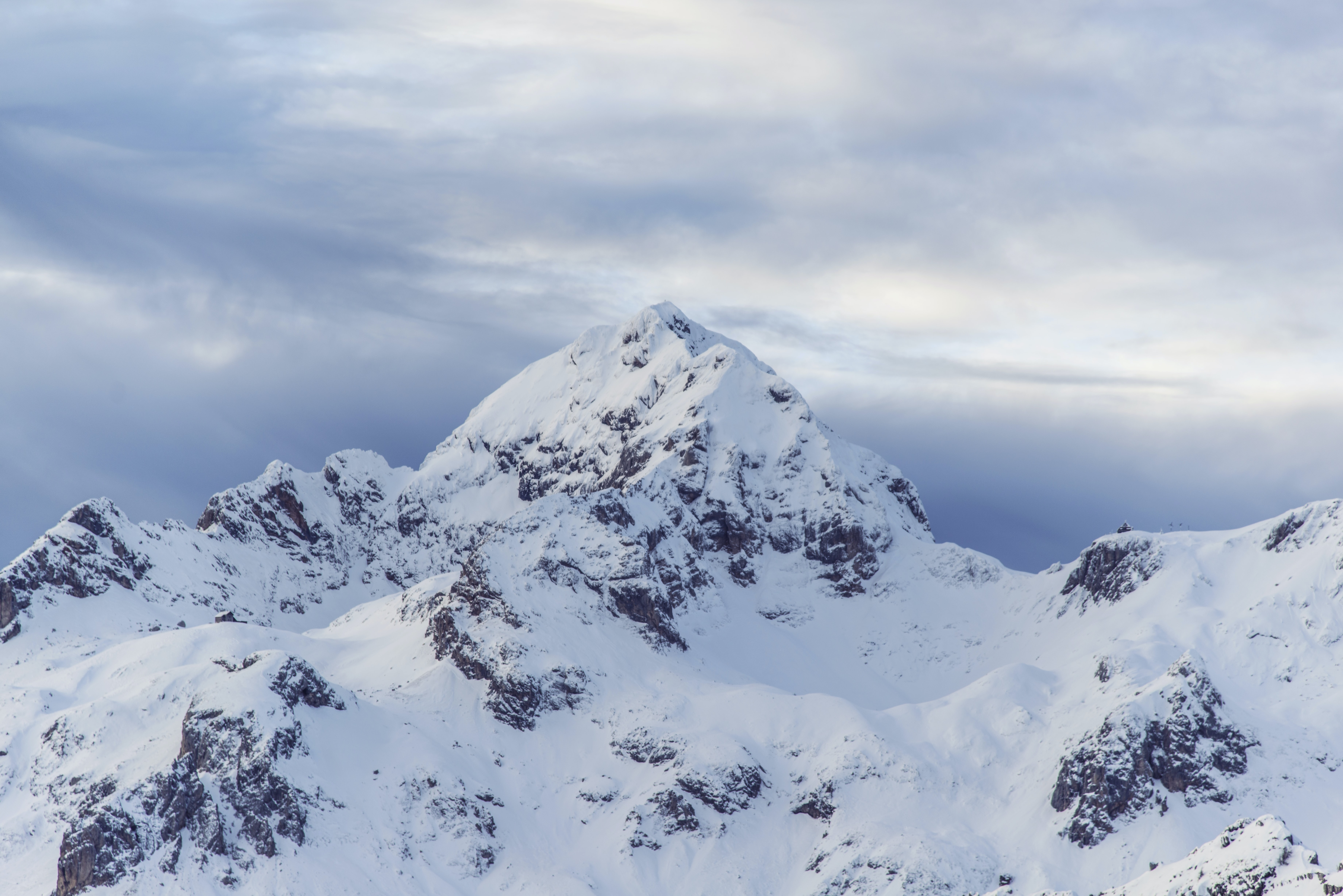 A rugged snow-capped mountain summit against an overcast sky