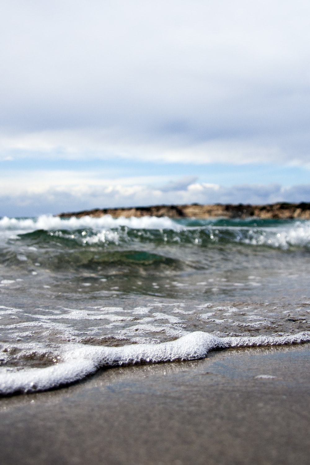 waves under white cloudy sky at daytime
