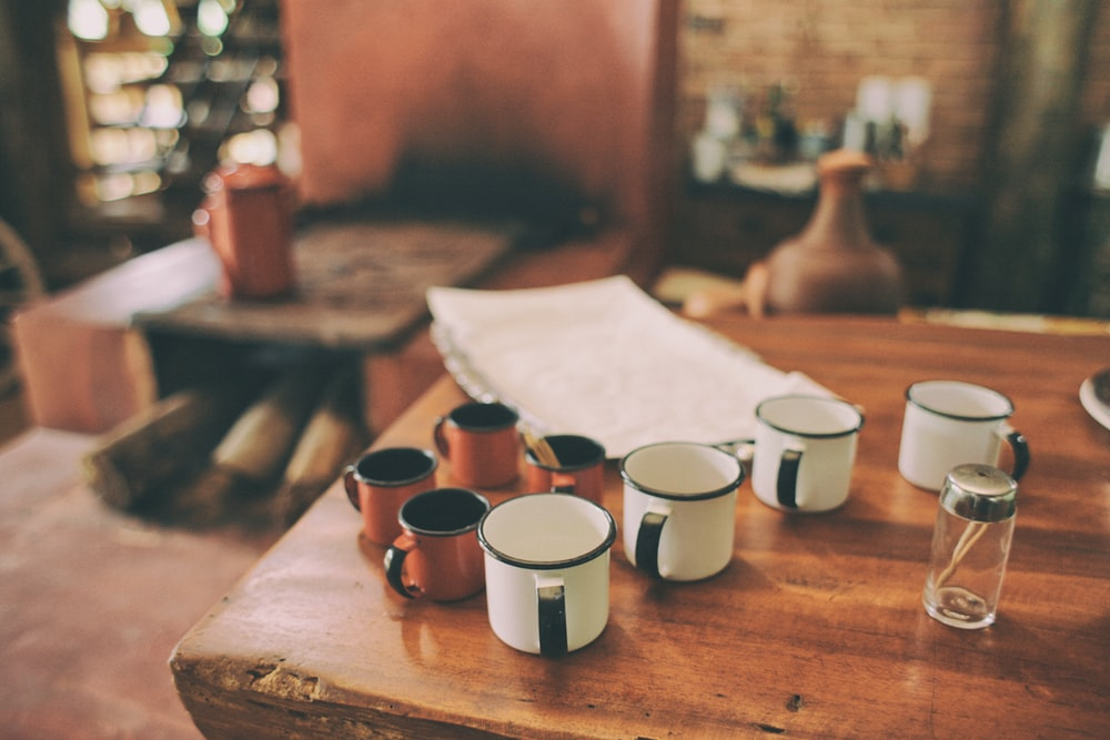 four white metal mugs on brown wooden table
