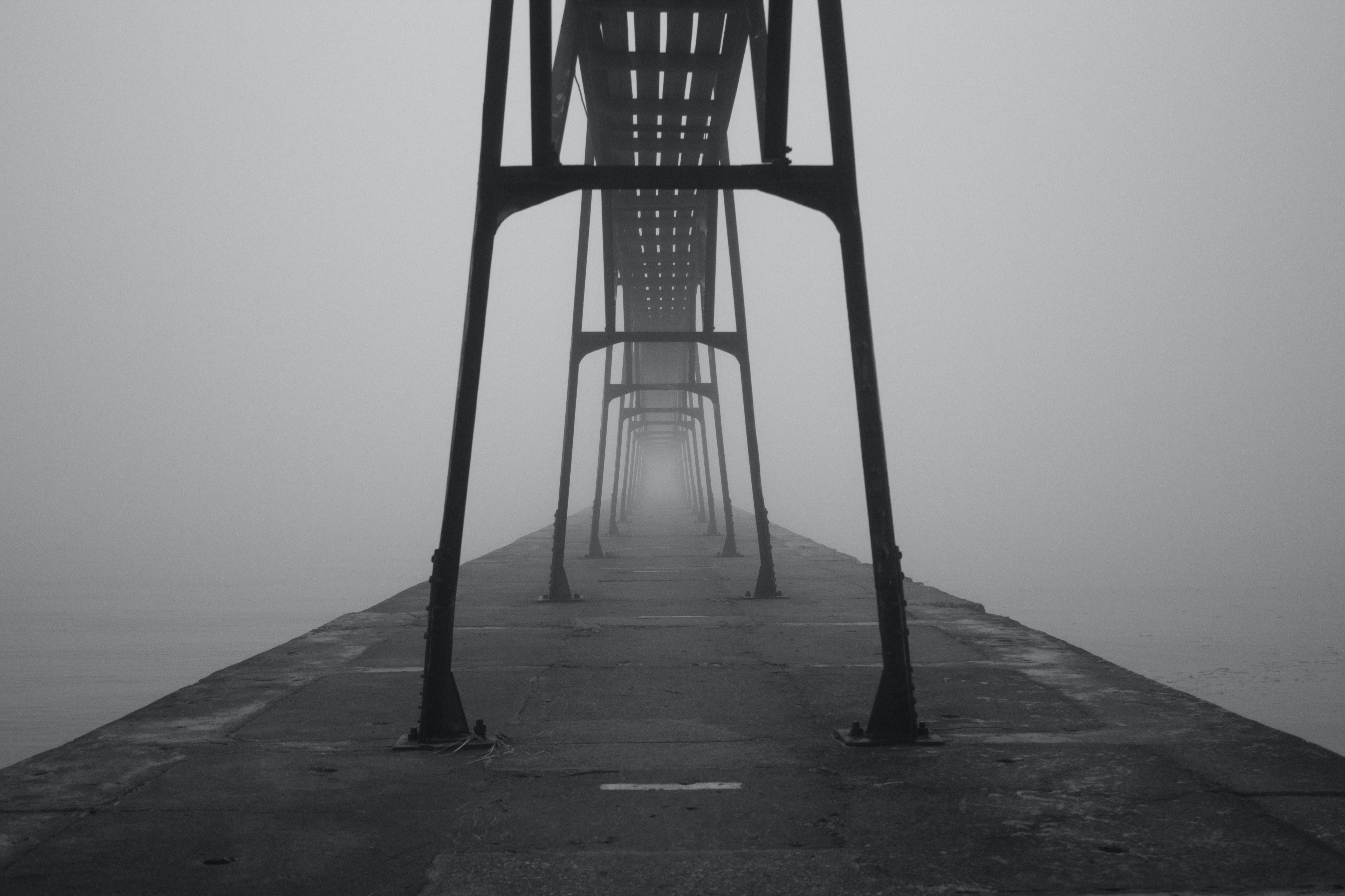 Foggy view of a steel bars on a pier near the ocean