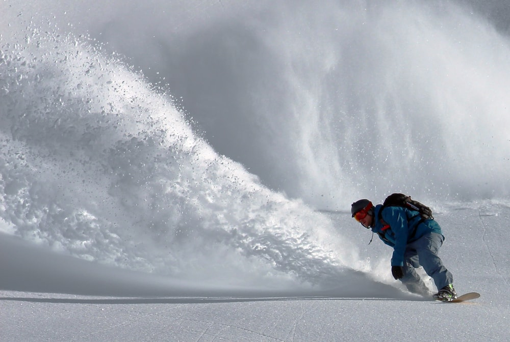 person gliding in snow during day time