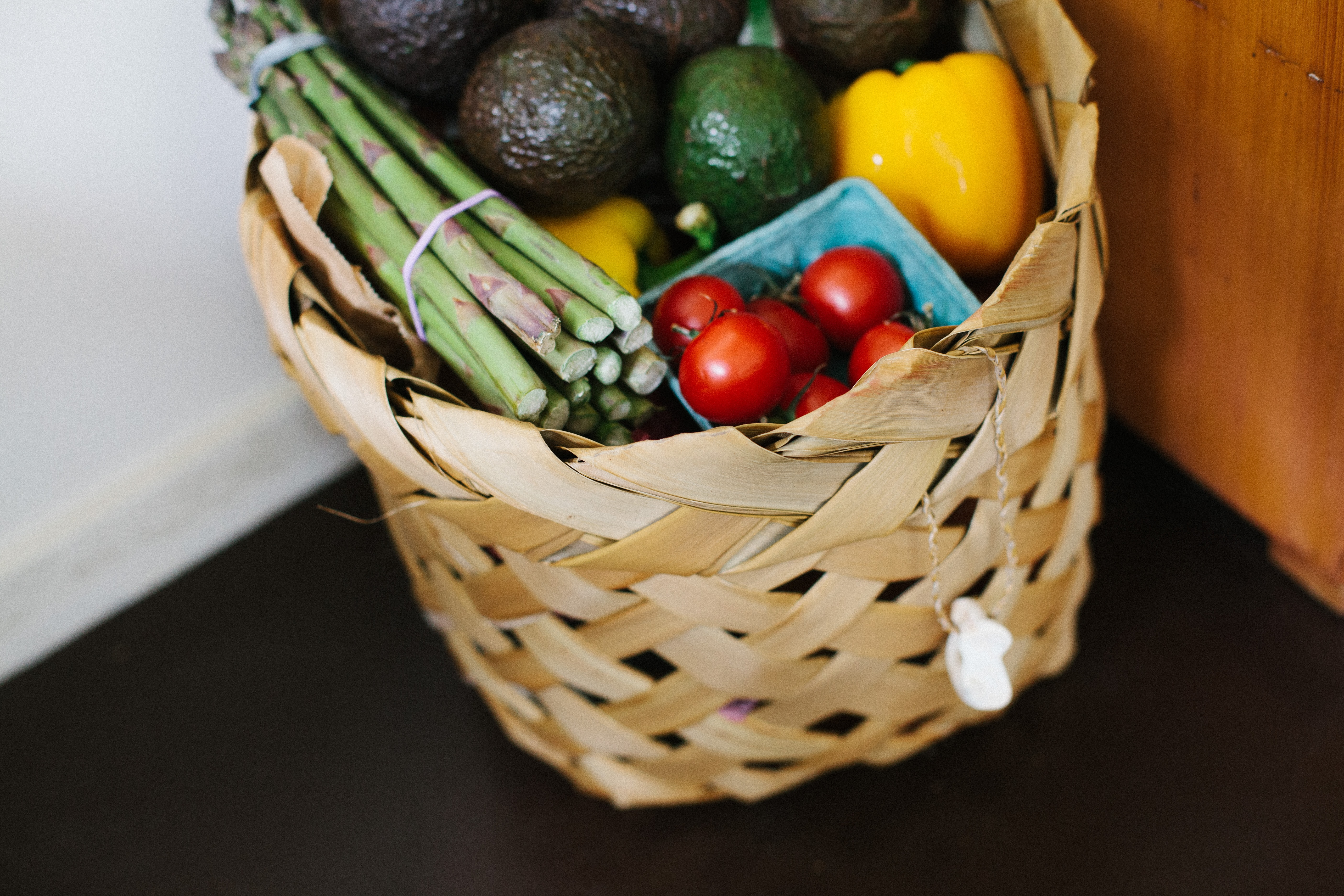 Basket of fresh produce with tomatoes, avocados, peppers, and asparagus