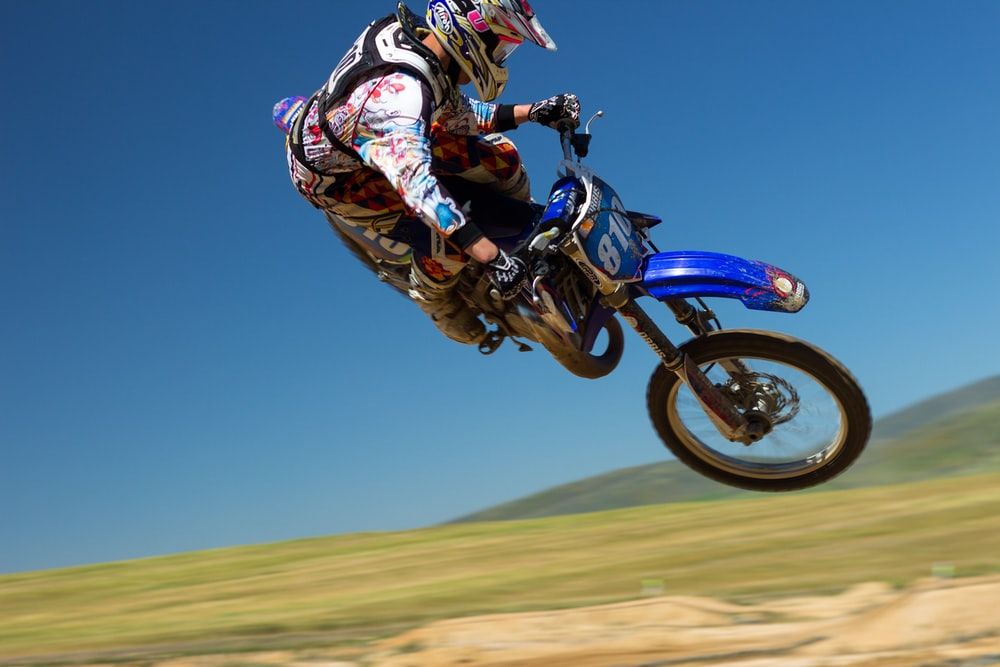 man doing motorcycle air stunt during daytime