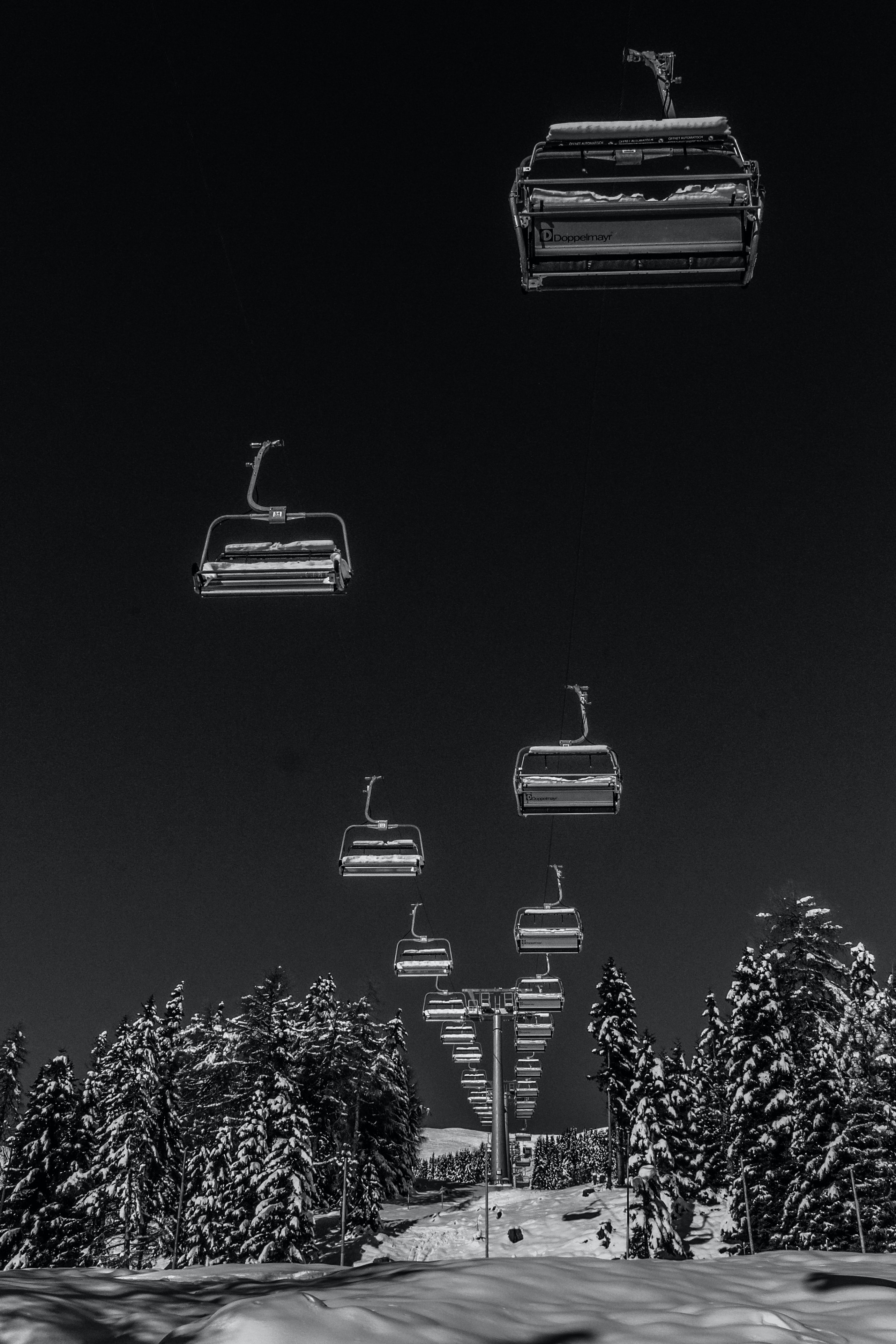 Black and white chairlift going through a snow covered park