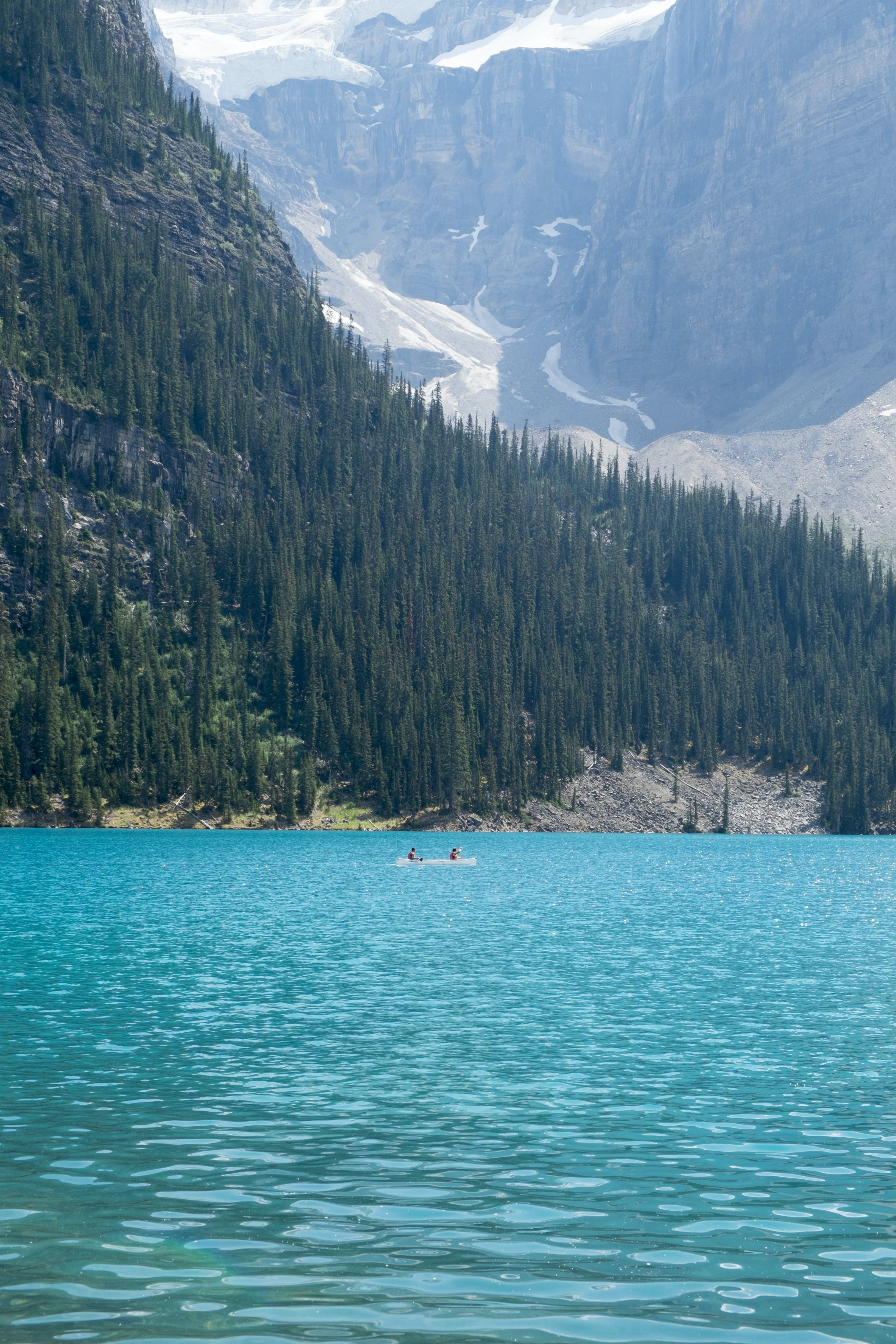 Broad landscape capturing the forest around the lake louise with people in a canoe