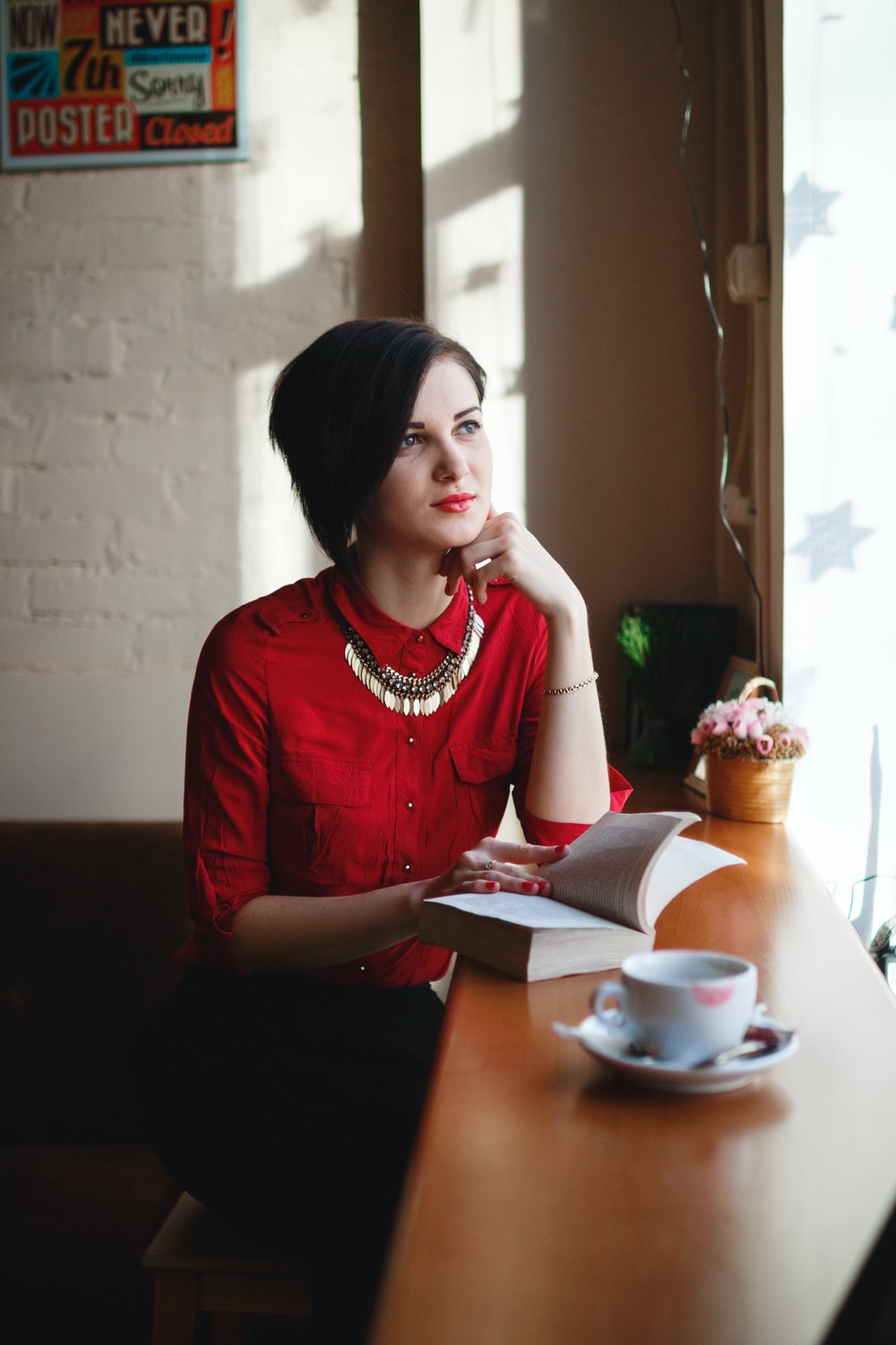 woman leaning on brown wooden table while holding book