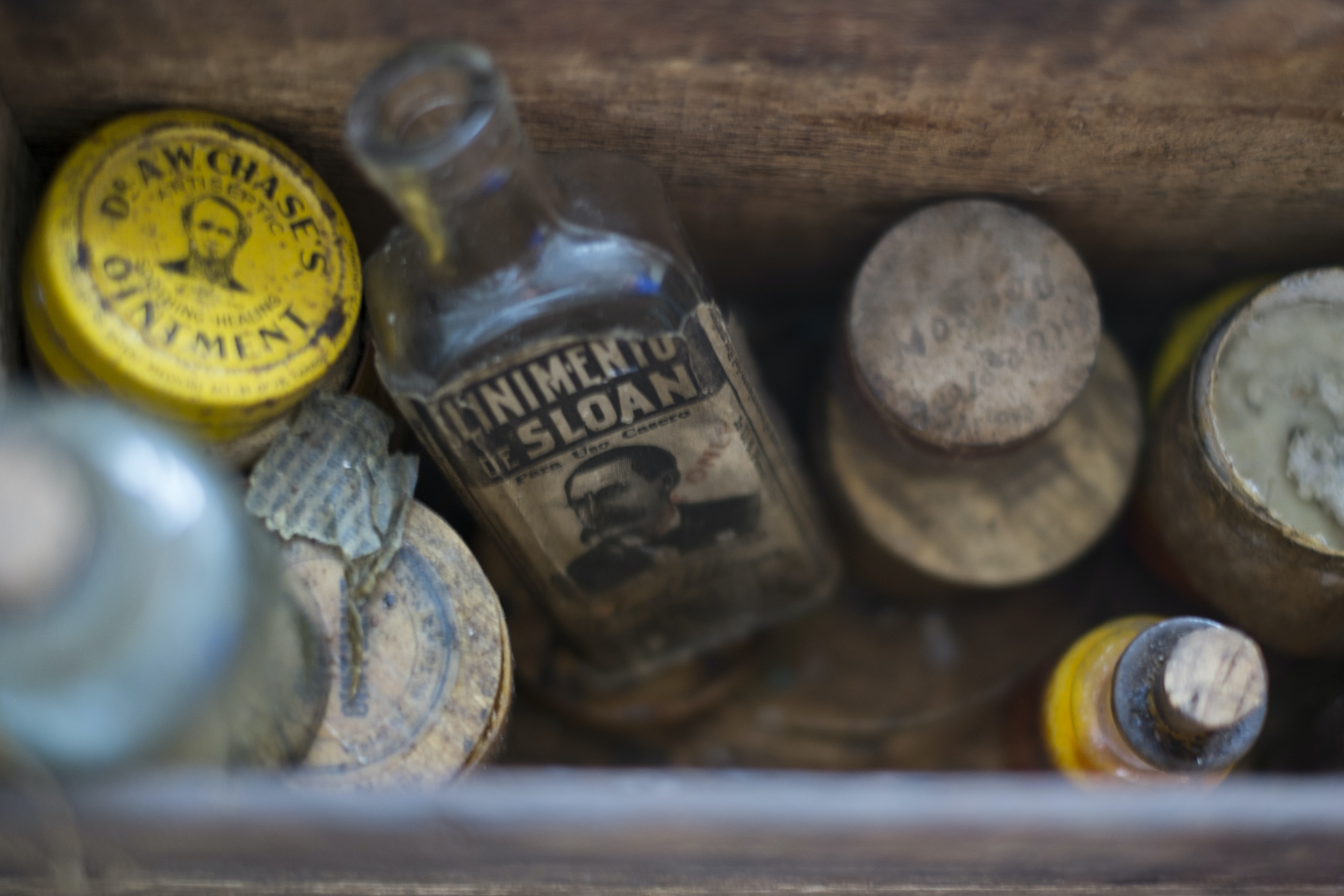 A wooden box filled with vintage medicinal jars and containers