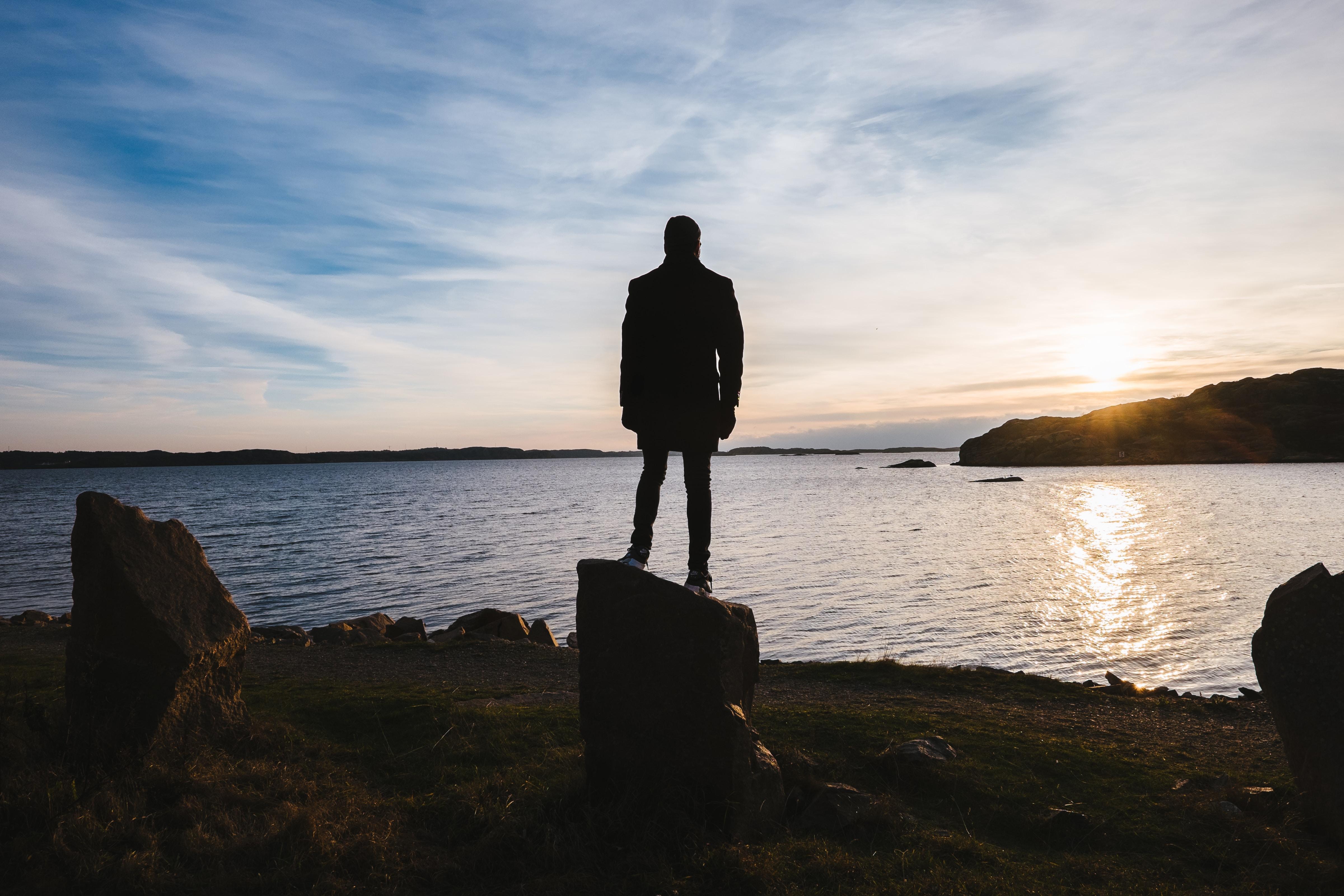 person standing on rock facing ocean