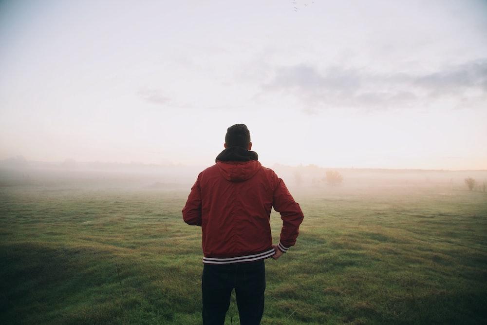 photo of man wearing red jacket facing horizon