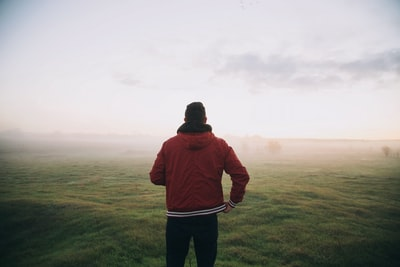 photo of man wearing red jacket facing horizon healthy teams background
