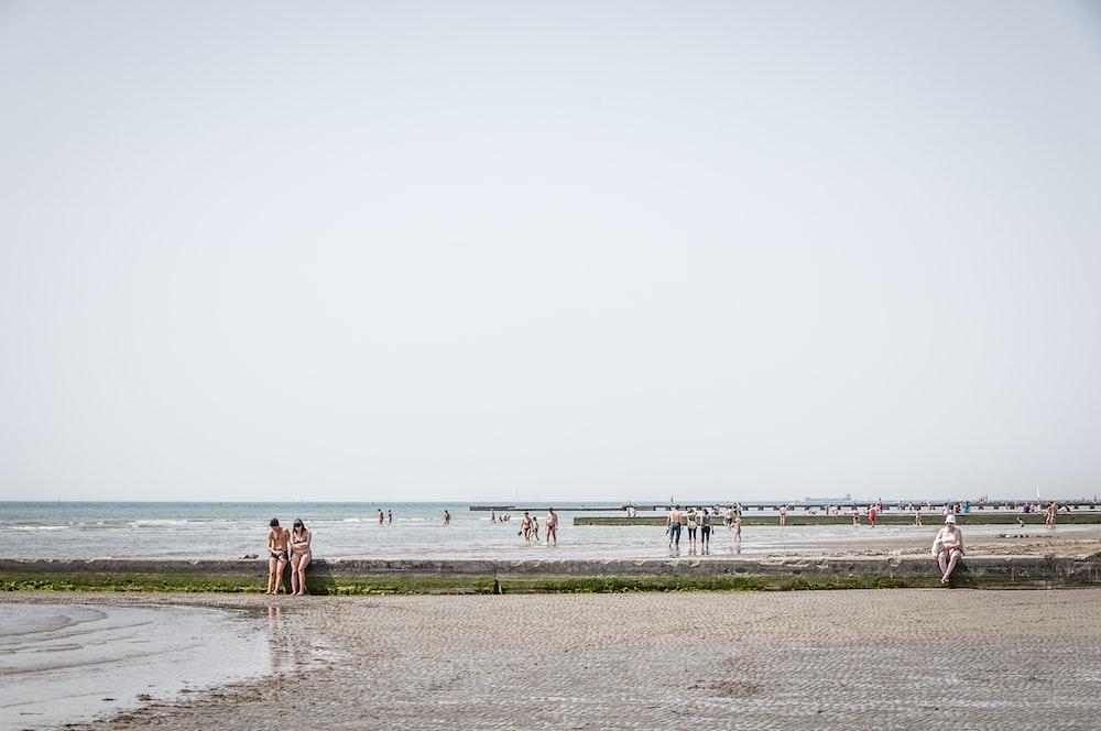 several people walking on seashore