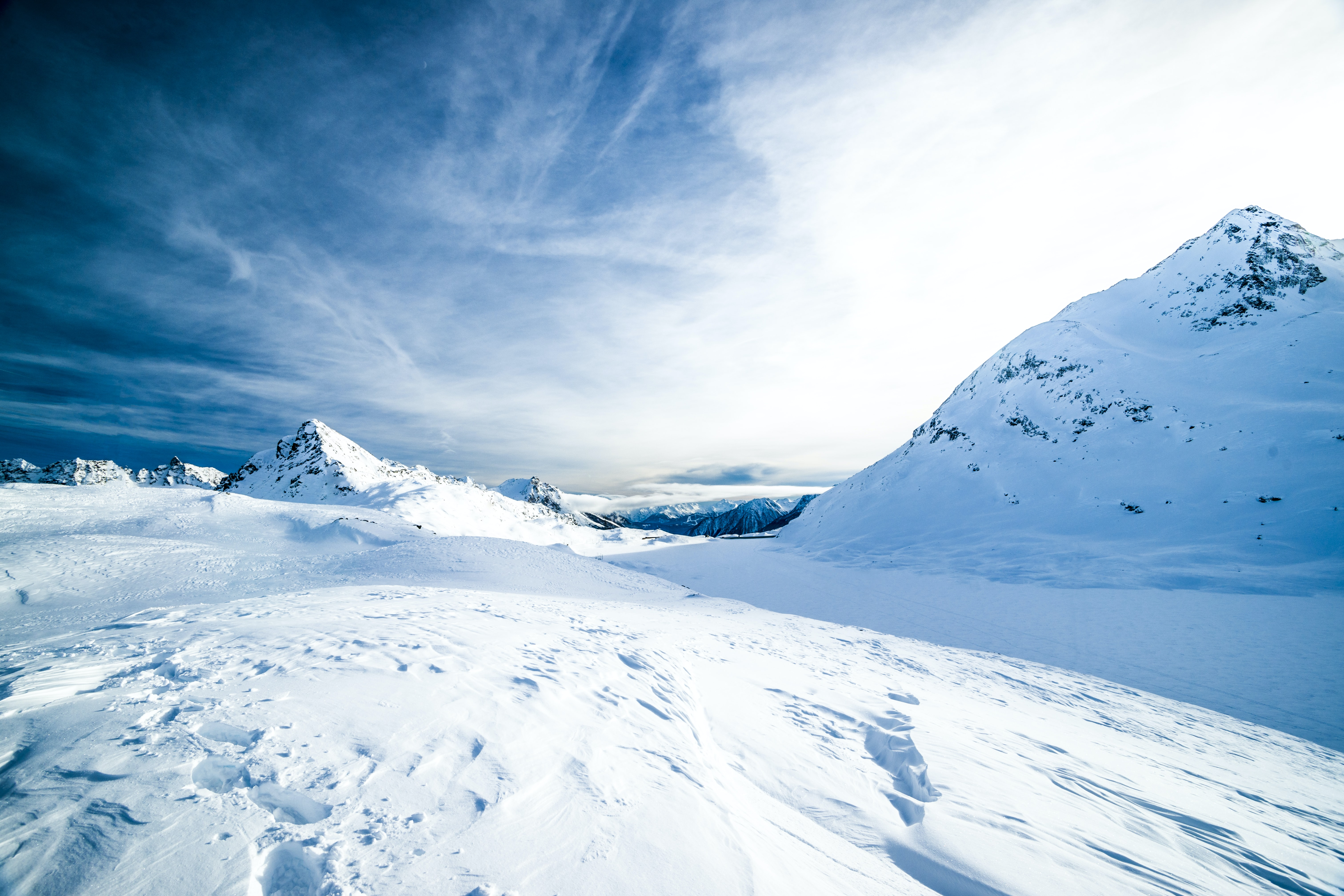 A frozen landscape with mountains coated with a thick layer of snow