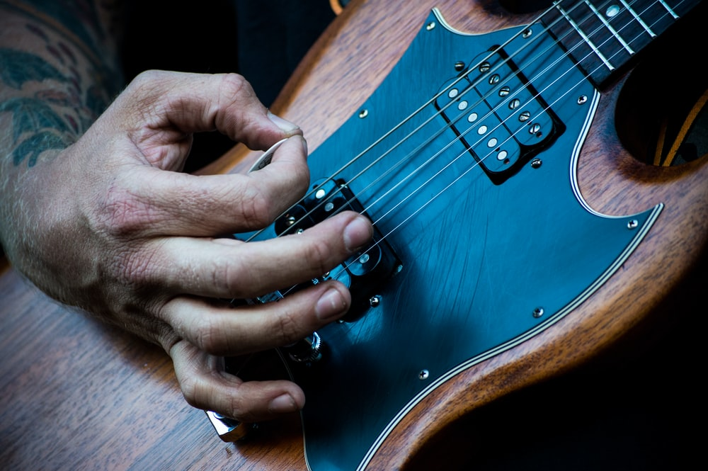 person plucking electric guitar with guitar pick