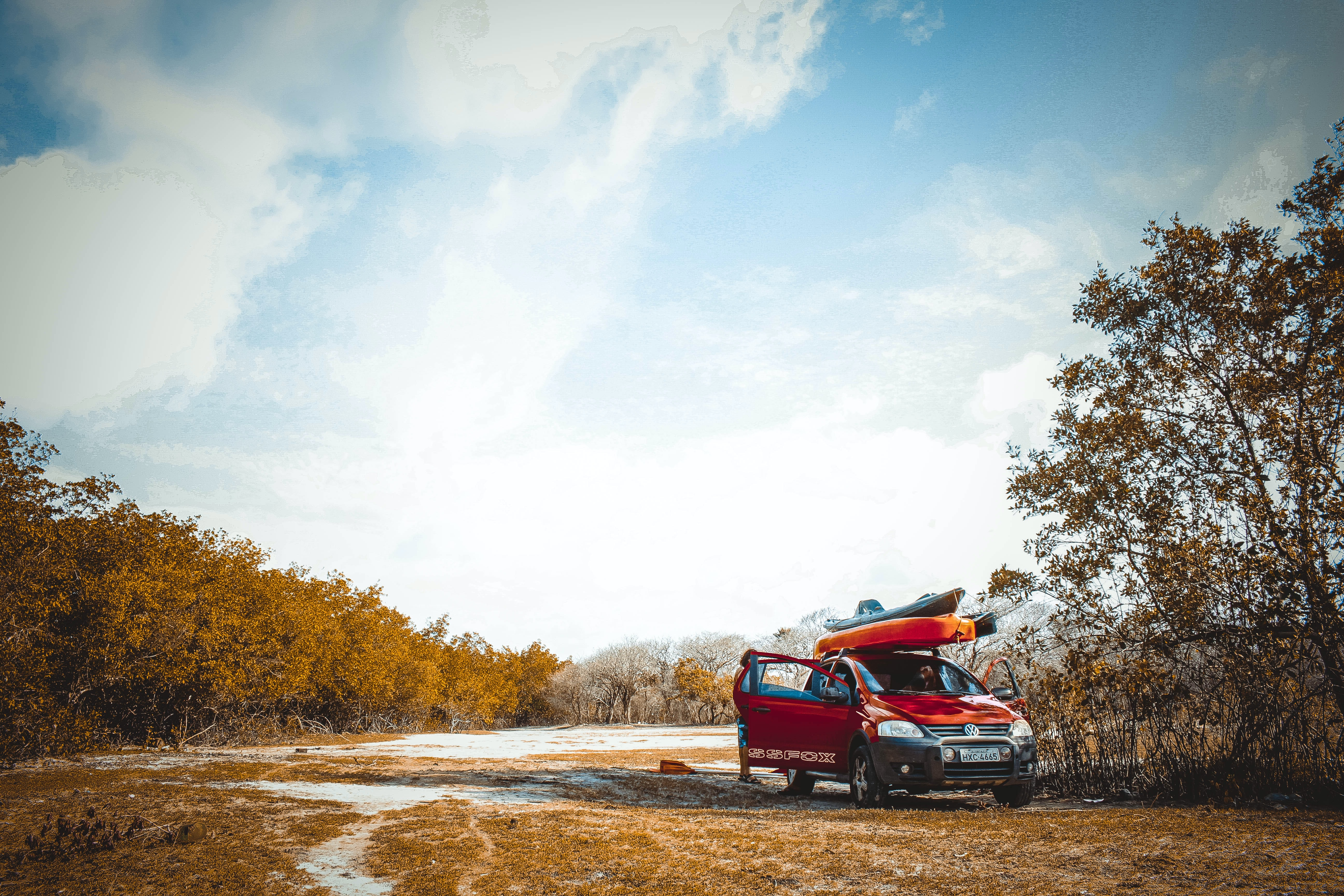 A red Volkswagen car with a kayak on top of it parked in the wilderness on an autumn's day