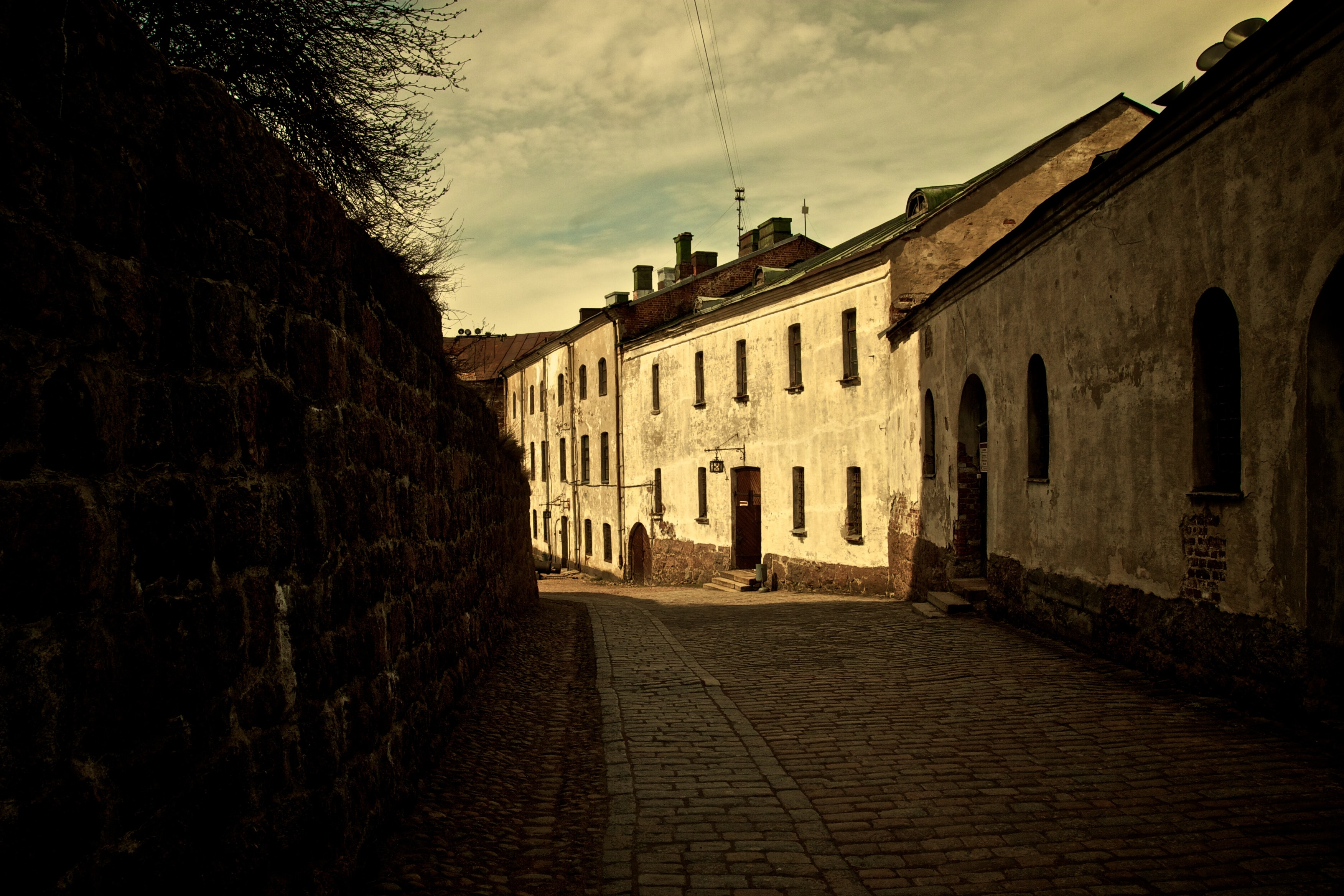 Brick street with sun illuminating a row of houses with arched windows and doorways