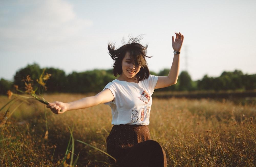 woman holding flower on field
