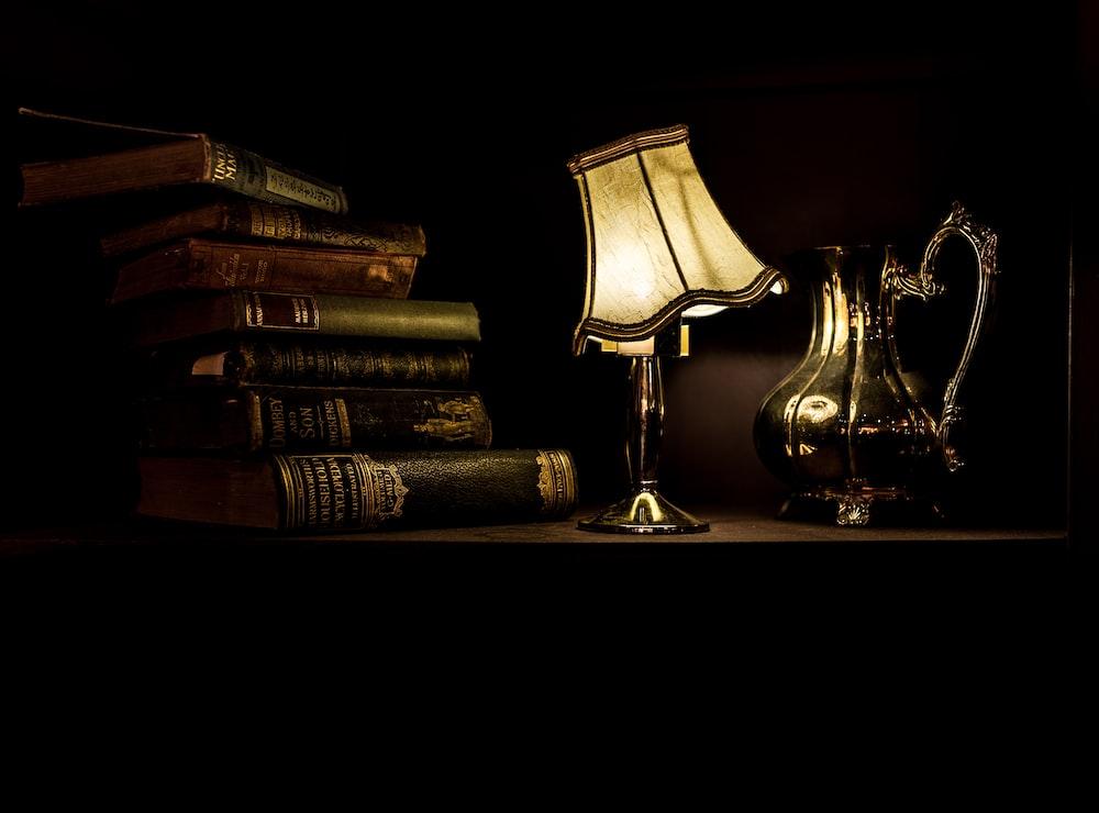 turned on desk lamp beside pile of books
