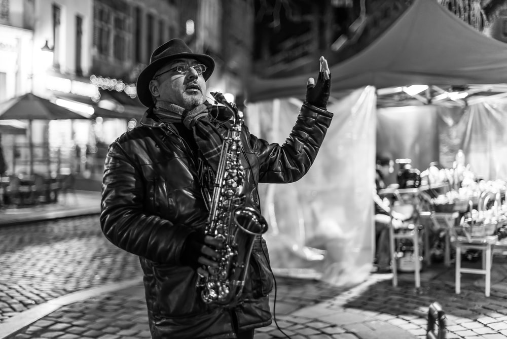 grayscale photo of man playing saxophone