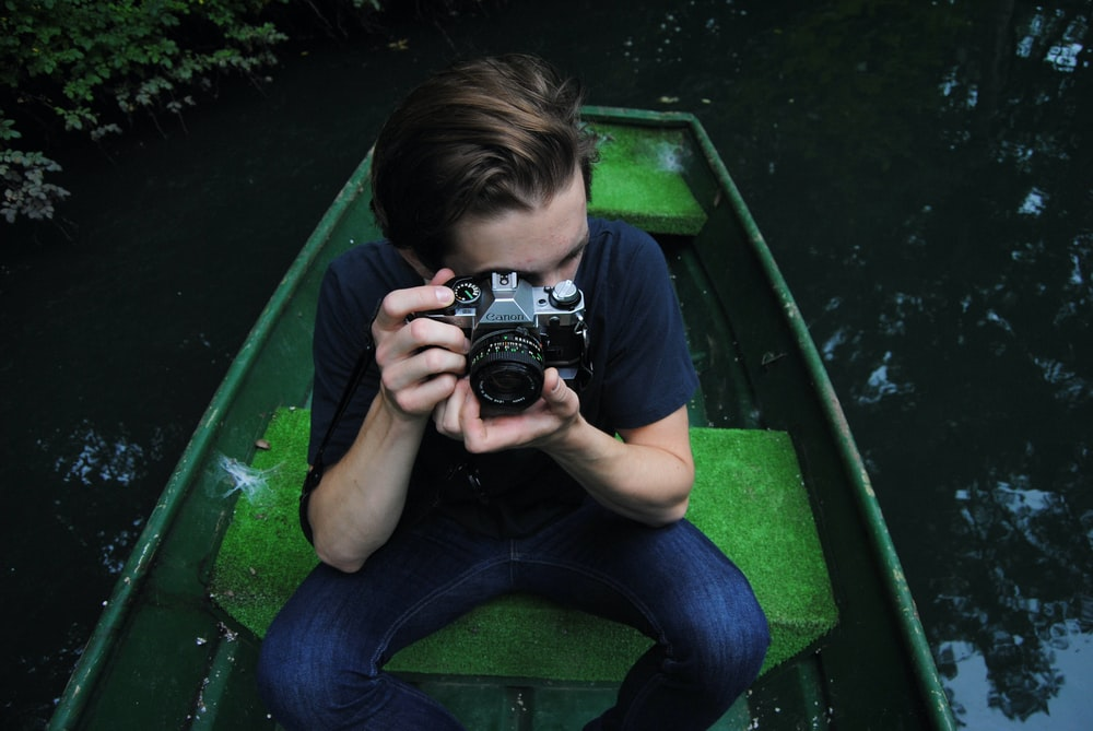man in black t-shirt and blue denim jeans riding on row boat holding bridge camera on focus photo